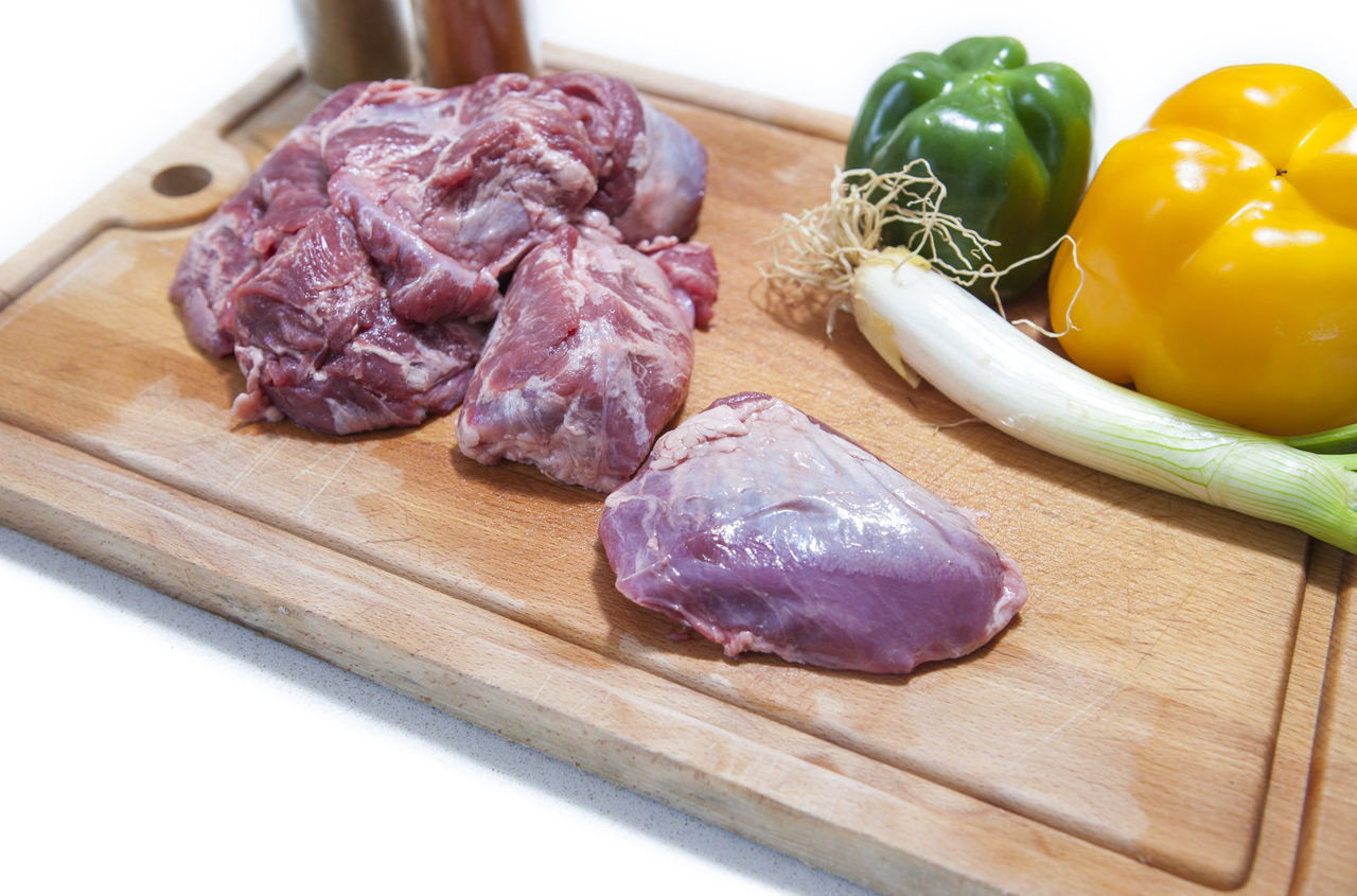 Raw meat cheek pieces of iberian pork with vegetables over wooden board. Isolated over white background Close-up Cutting Board Day Domestic Kitchen Domestic Room Food Food And Drink Freshness Garlic Garlic Bulb Garlic Clove Ground Beef Healthy Eating Indoors  Ingredient Meat Minced No People Raw Food SLICE Still Life Table Vegetable Wood - Material