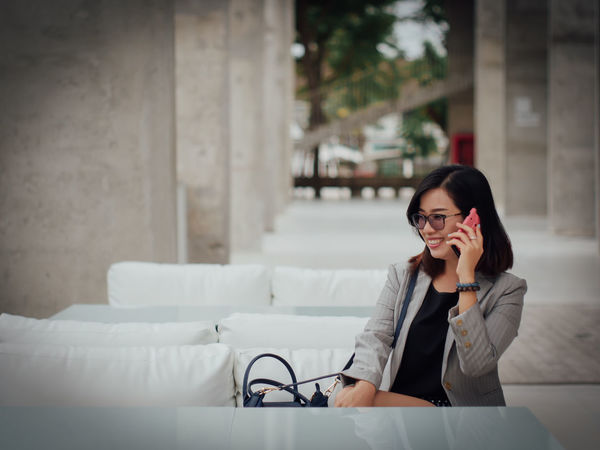 Answering Architecture Built Structure Communication Connection Day Eyeglasses  Happiness Indoors  Listening Mobile Phone One Person People Portable Information Device Real People Sitting Table Talking Technology Telephone Using Phone Wireless Technology Young Adult Young Women