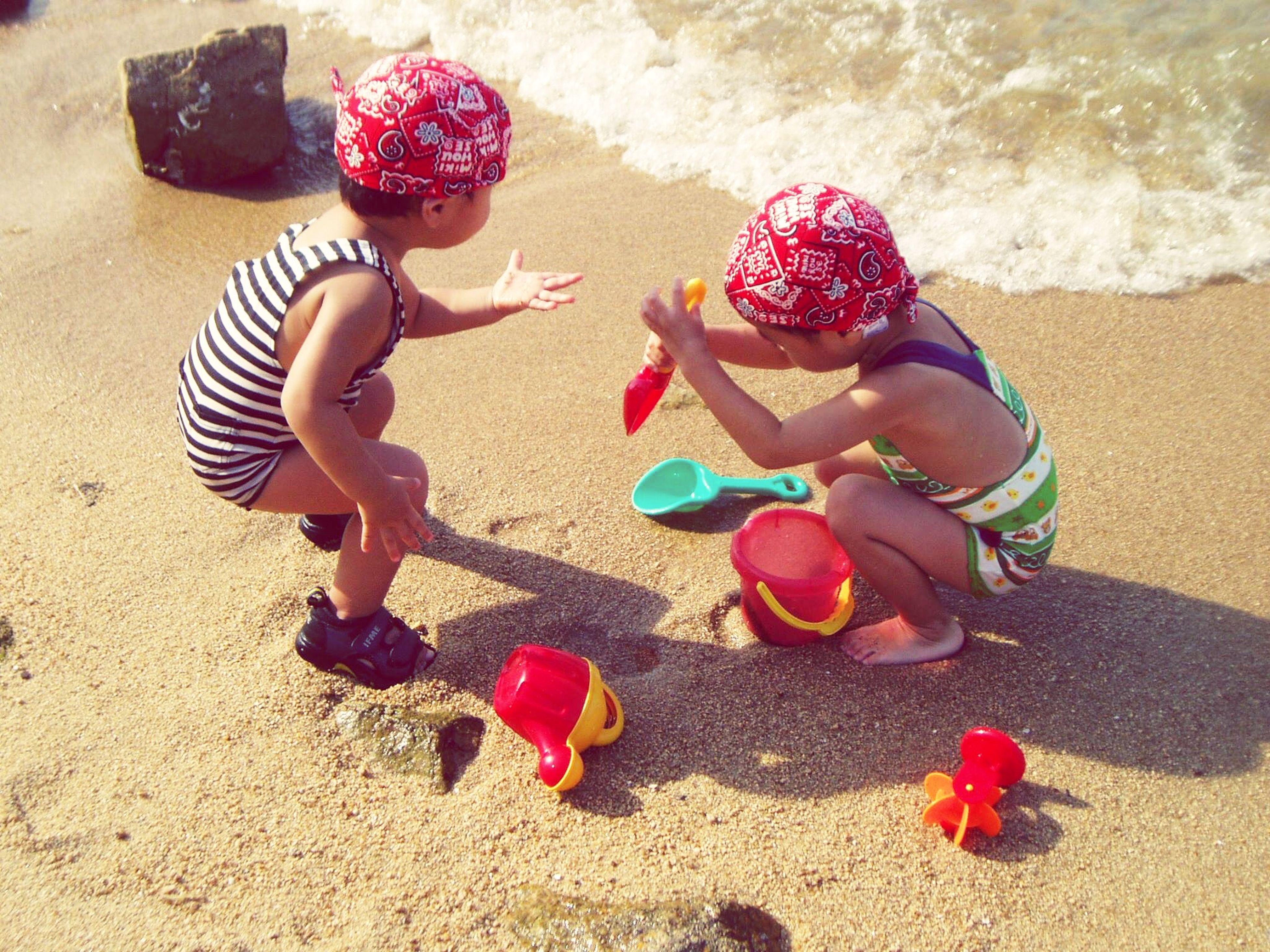 sand, beach, high angle view, sunlight, red, childhood, shadow, shore, day, lifestyles, leisure activity, person, outdoors, pink color, toy, love, vacations, still life