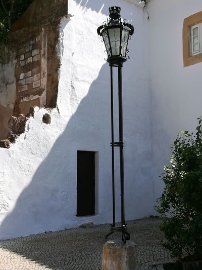 Street Light No People Architecture Outdoors Illuminated Day Sky Built Structure Blue And White Sky Albufeira Portugal Been There. Done That. Architecture Travel Destinations Sunlight Summer Vacations Wall Historical Building Focus On Foreground Building Exterior