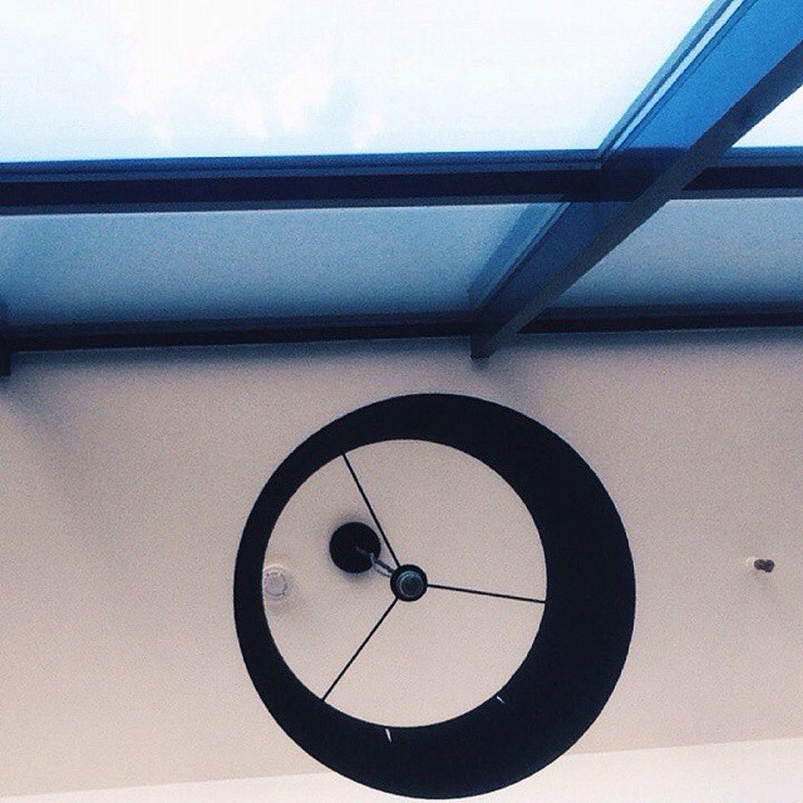 indoors, low angle view, architecture, built structure, circle, clock, directly below, wall - building feature, time, geometric shape, ceiling, technology, wall, electricity, no people, close-up, lighting equipment, copy space, day, communication