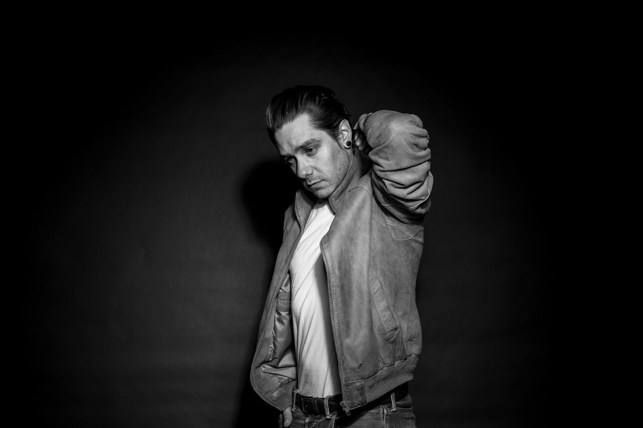 Clichéd studio shot of a greaser/ rockabilly with a white t-shirt and a leather jacket in black and white 50s Adult Black And White Black Background Blond Hair Front View Greaser James Dean Leather Jacket One Man Only One Person Portrait Rockabilly Studio Shot Young Adult