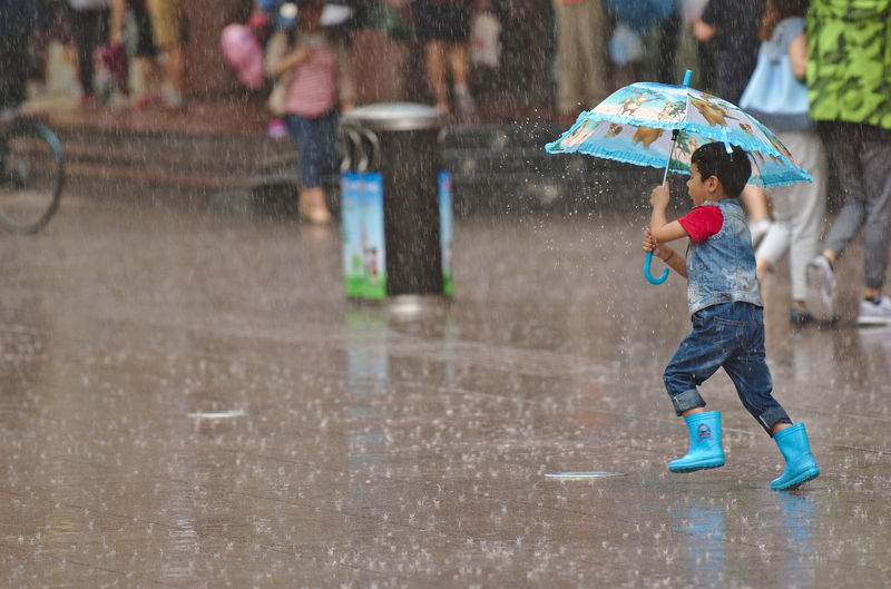 NANJING南京CHINA中国BEAUTY Nanjing Road Shanghai Streets Action Shot  Blue Boots Childhood Focus On Foreground Fun Leisure Activity Motion One Boy Only One Person Outdoors Playing Rain Real People Splashing Spraying Umbrella Water Wet