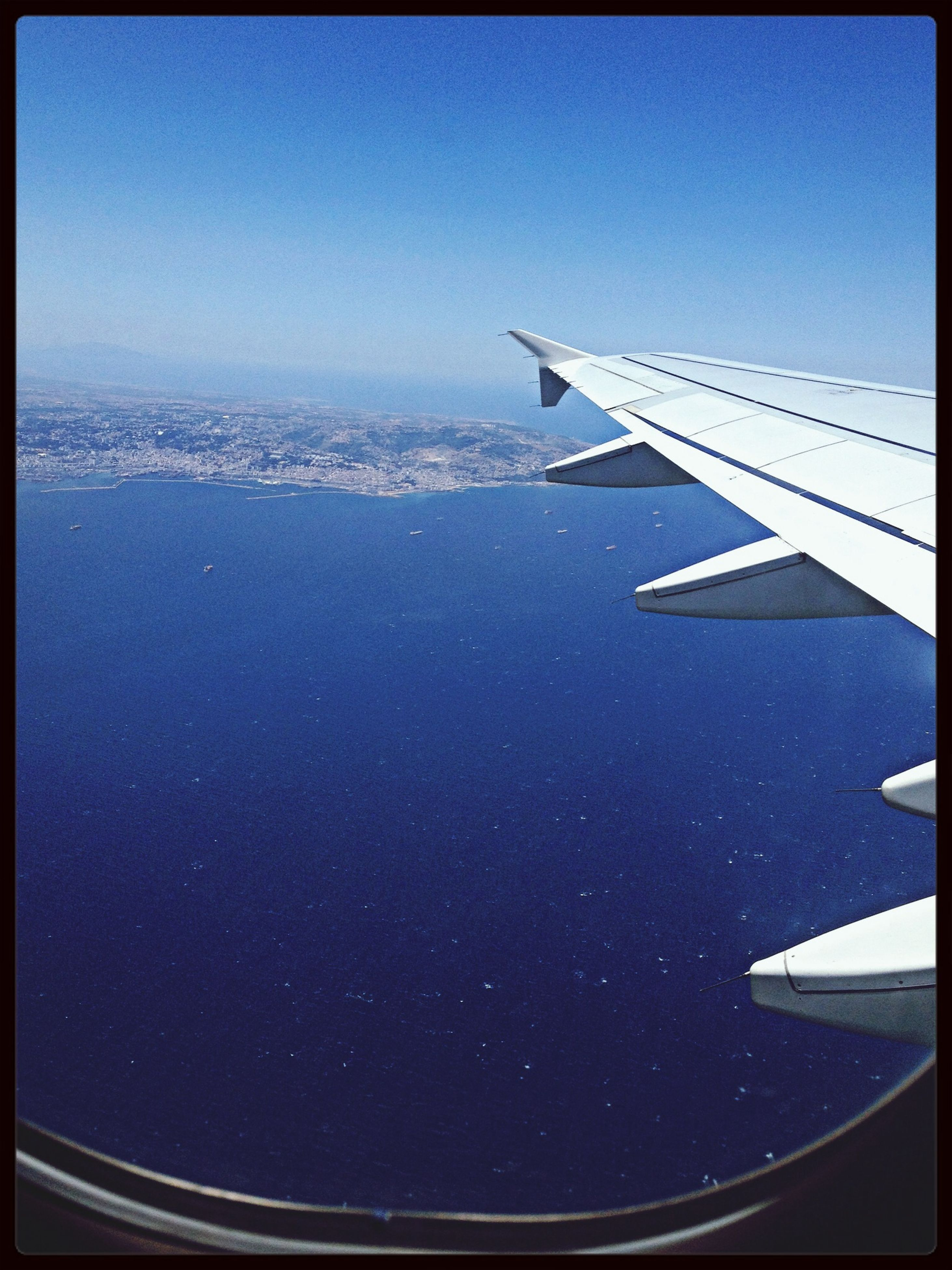 airplane, aircraft wing, air vehicle, flying, transportation, mode of transport, aerial view, part of, cropped, blue, travel, journey, airplane wing, mid-air, sky, aeroplane, clear sky, on the move, scenics, sea
