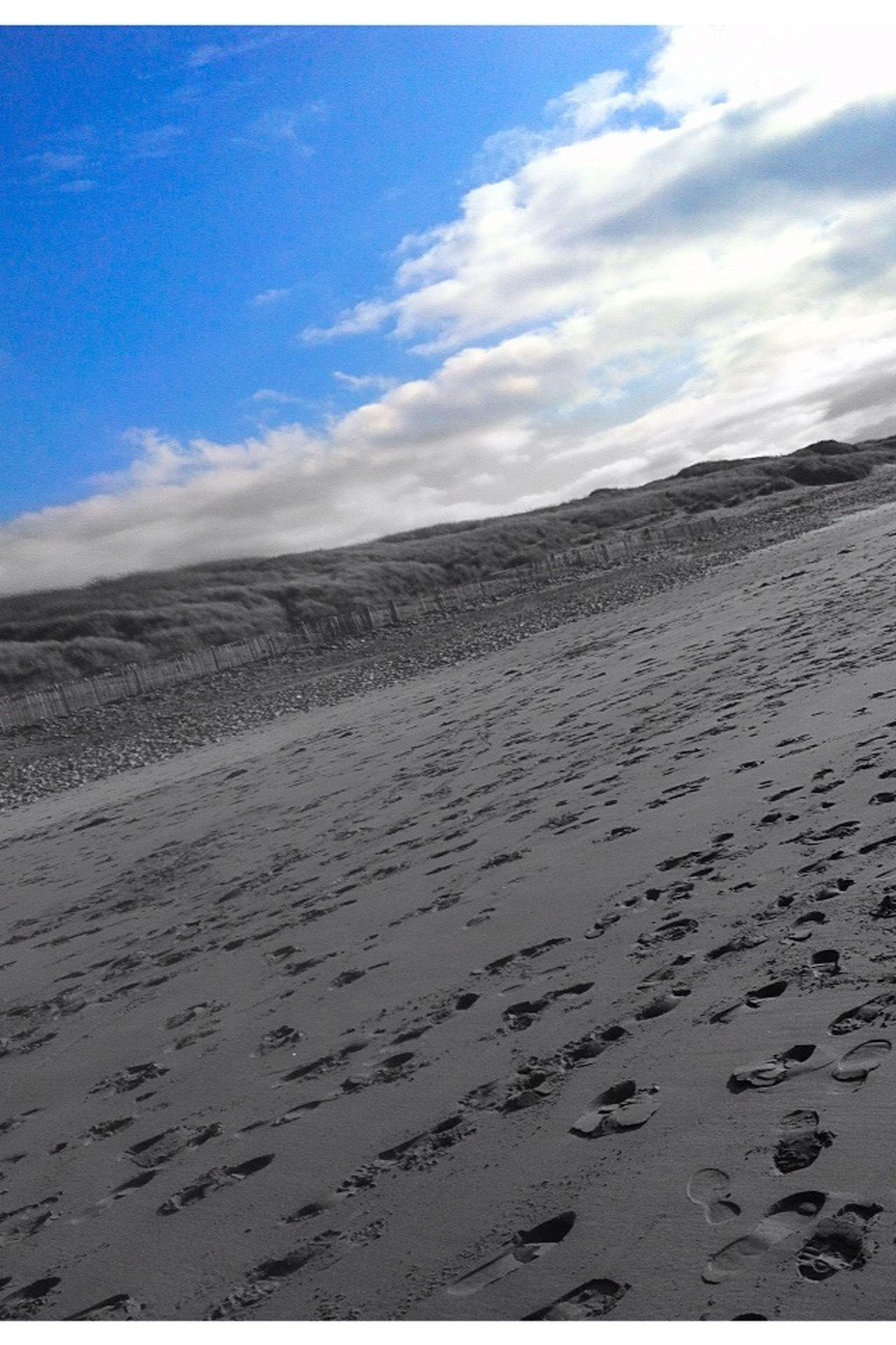 sand, beach, sky, tranquil scene, tranquility, scenics, beauty in nature, nature, sea, cloud - sky, shore, footprint, landscape, cloud, remote, idyllic, sand dune, day, desert, non-urban scene