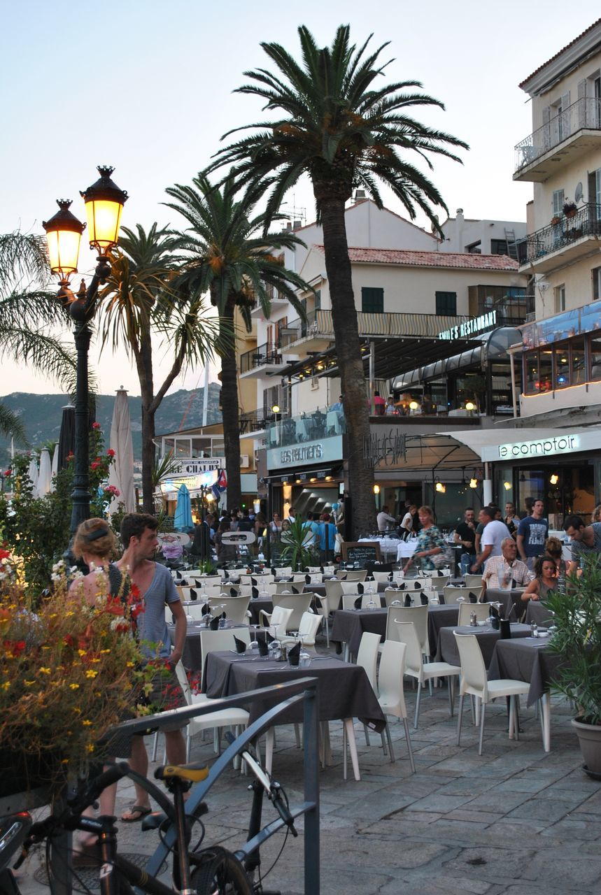 table, chair, outdoor cafe, restaurant, sidewalk cafe, tree, large group of people, cafe, building exterior, outdoors, palm tree, real people, architecture, built structure, men, day, lifestyles, women, sitting, group of people, city, clear sky, sky, people