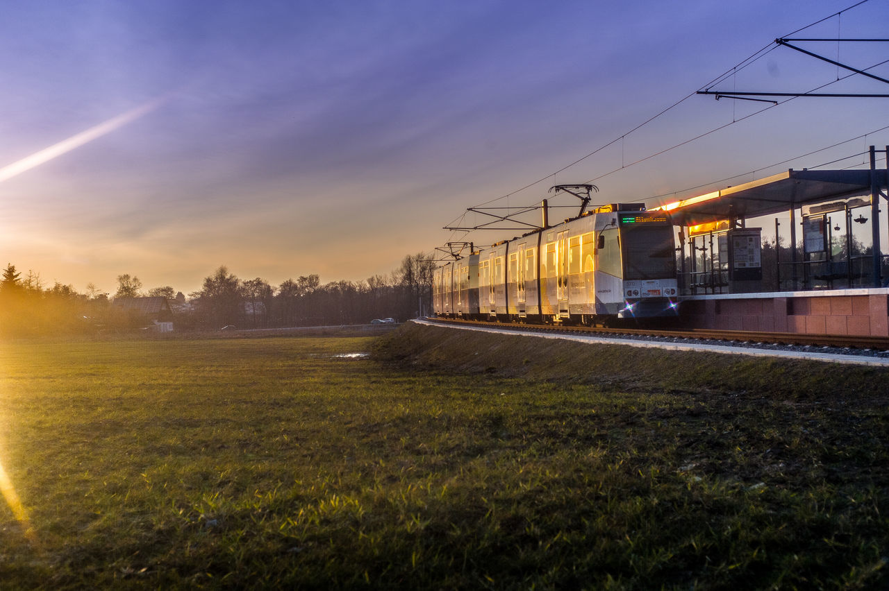 transportation, rail transportation, sky, sunset, nature, cable, train - vehicle, grass, railroad track, public transportation, no people, built structure, outdoors, architecture, electricity pylon, building exterior, beauty in nature, tree, day