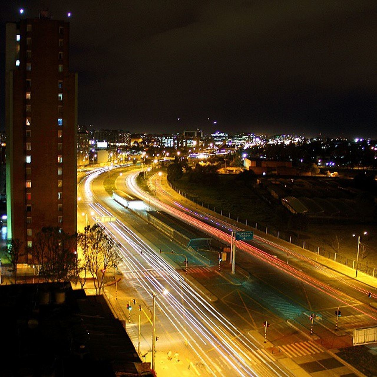 illuminated, night, light trail, speed, long exposure, transportation, motion, traffic, high street, city, road, high angle view, street light, city life, street, no people, outdoors, building exterior, built structure, architecture, cityscape, urban scene, sky