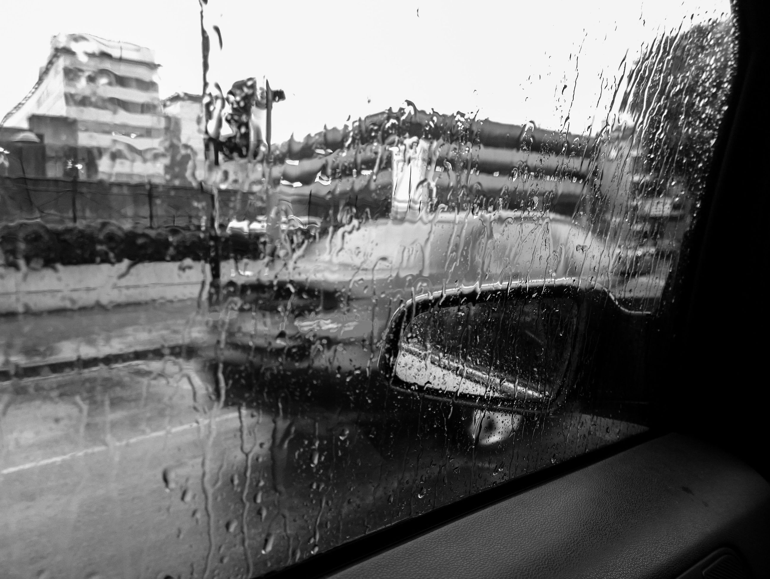 water, architecture, building exterior, built structure, wet, transportation, motion, mode of transport, drop, fountain, rain, car, city, splashing, land vehicle, glass - material, street, transparent, spraying, window