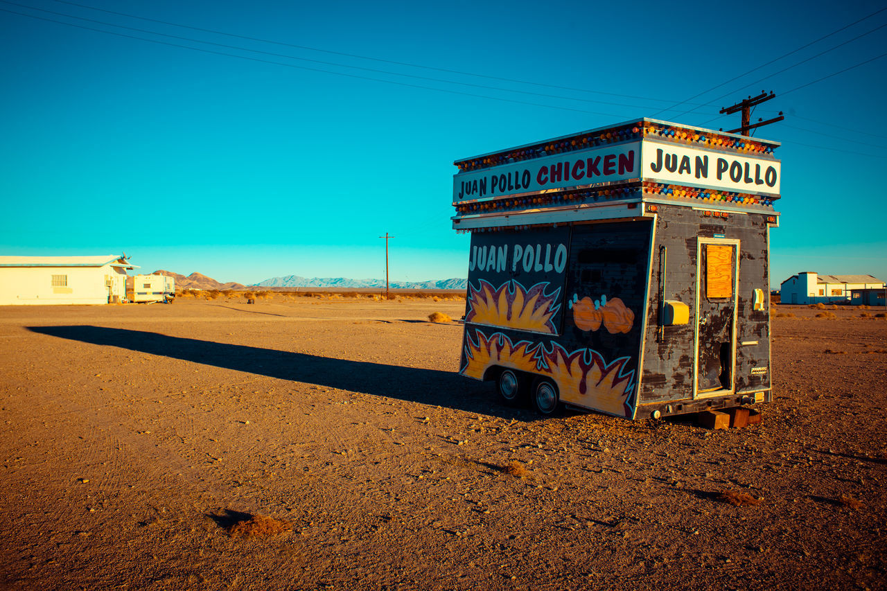 text, communication, outdoors, clear sky, day, no people, blue, transportation, architecture, sand, built structure, sky, telephone booth