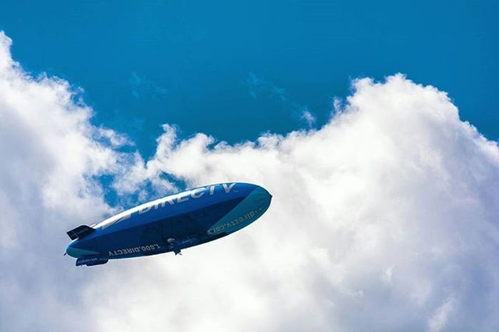This DirectTV blimp was floating through the partly cloudy skies of Boston, Massachusetts. Blue Direct Tv Cloudy Bluesky Blimp Baloon Air Fluffy Itssofluffy White Follow Lfl Instafollow Family Thisisnotasponsorship Wishitwas Followme Instadaily Ztprod