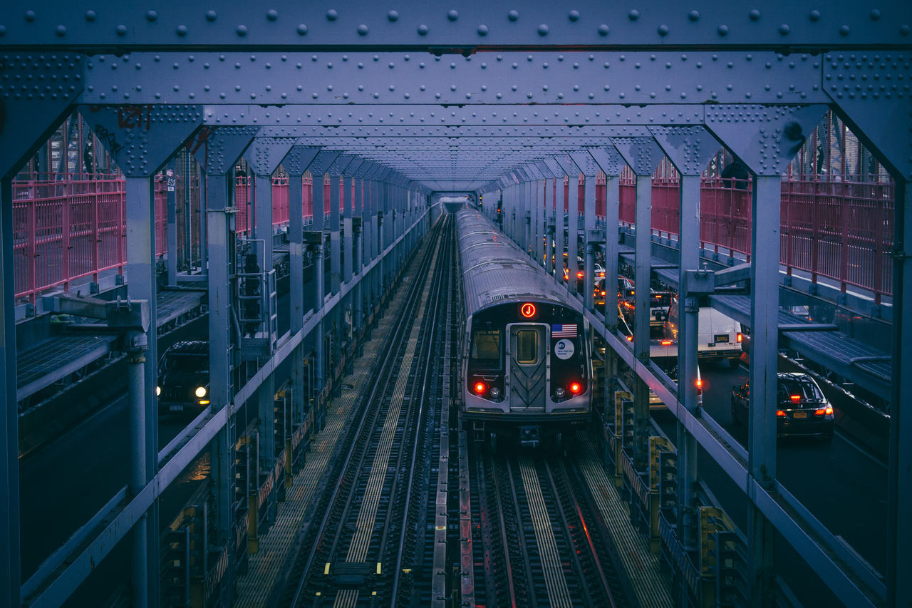 transportation, mode of transport, public transportation, rail transportation, railroad track, built structure, land vehicle, the way forward, illuminated, bridge - man made structure, railroad station platform, train - vehicle, architecture, no people, indoors, night, sky