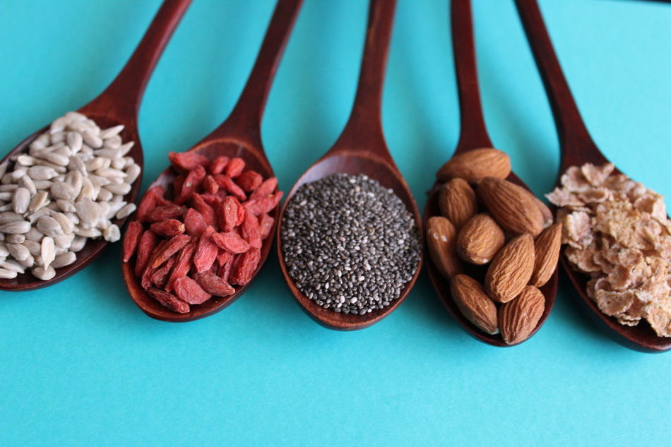 Healthy seeds on five wood spoons over blue background Almonds Blue Background Chia Seed Close-up Food Food And Drink Gojiberries Healthy Eating Indoors  No People Oat Raw Food Still Life Sunflower Seeds Table Top View Of Food Variation Wood Spoon