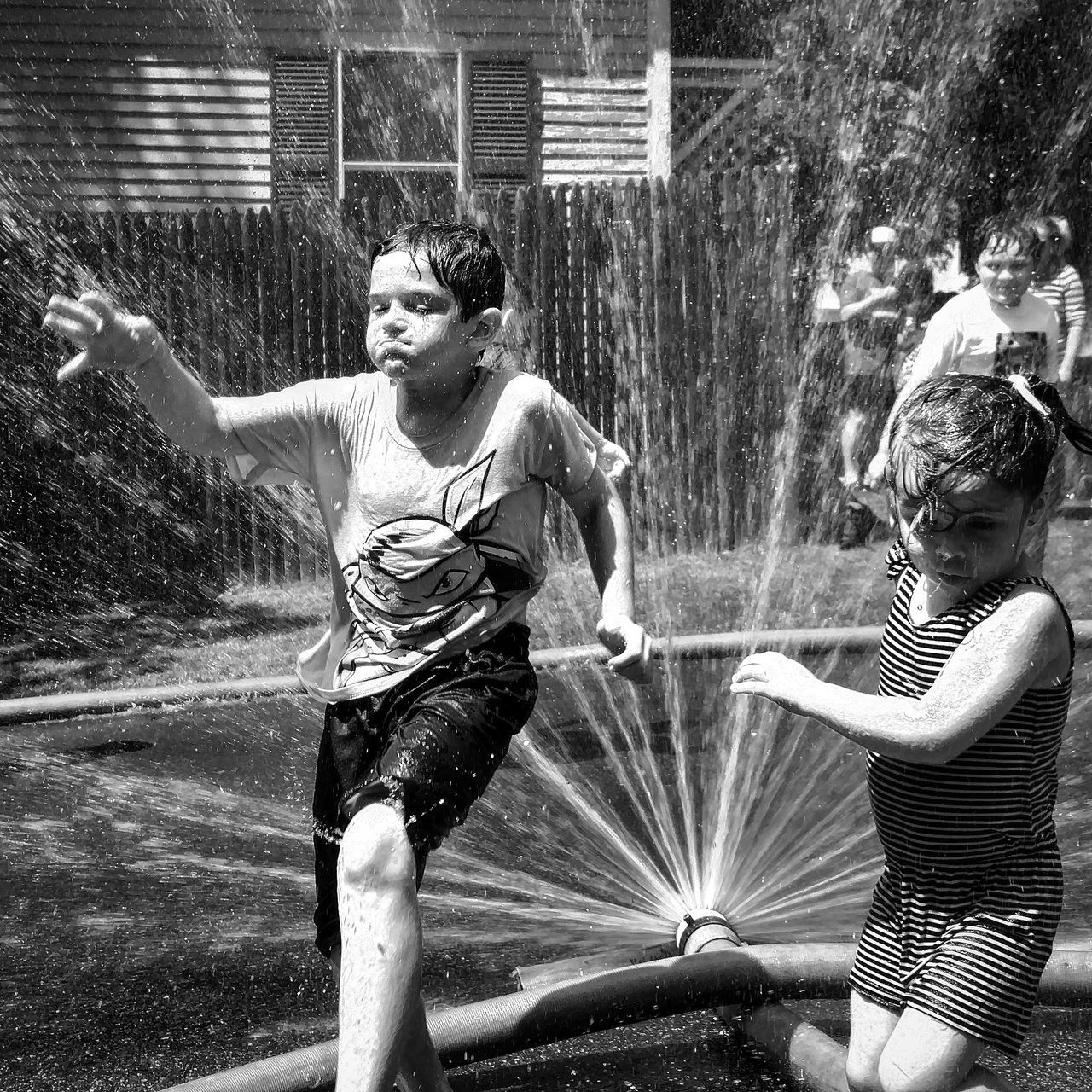 water, spraying, real people, motion, outdoors, casual clothing, splashing, two people, day, sprinkler, leisure activity, lifestyles, childhood, boys, standing, girls, togetherness, building exterior, young adult, nature, people