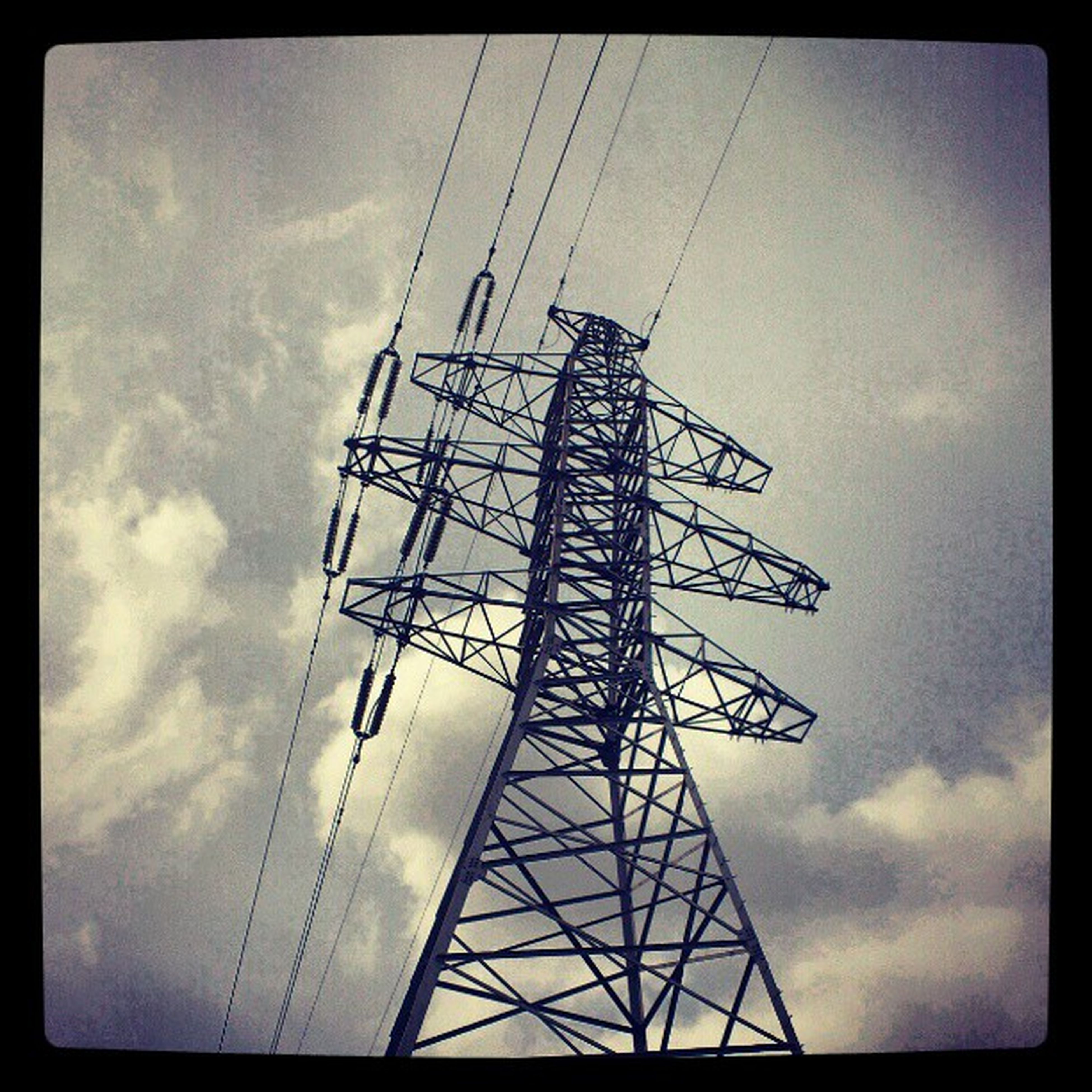 low angle view, sky, transfer print, cloud - sky, auto post production filter, fuel and power generation, electricity pylon, technology, tall - high, cloudy, power supply, electricity, cloud, metal, silhouette, connection, power line, day, tower, outdoors