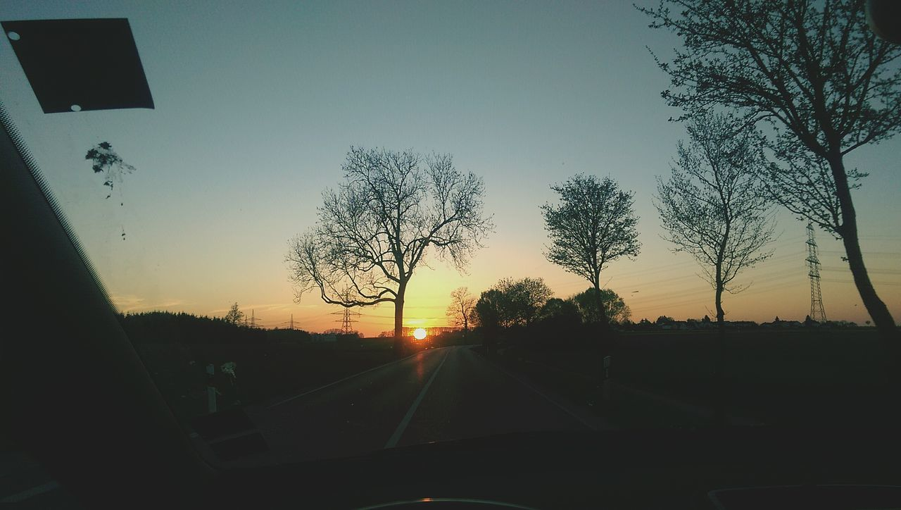 car, vehicle interior, tree, transportation, car interior, sunset, windshield, land vehicle, silhouette, mode of transport, sky, no people, road, car point of view, the way forward, nature, scenics, beauty in nature, clear sky, day, outdoors