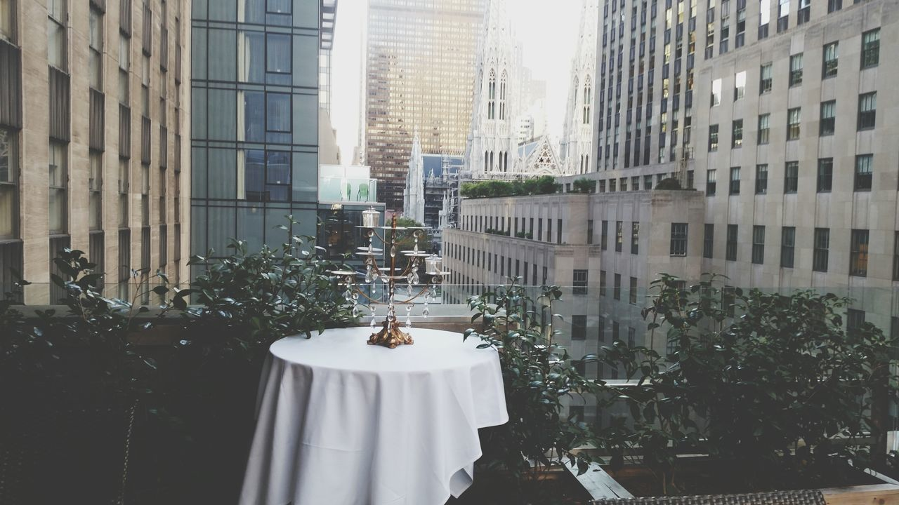 Candlestick Holder On Table In Balcony Against Buildings