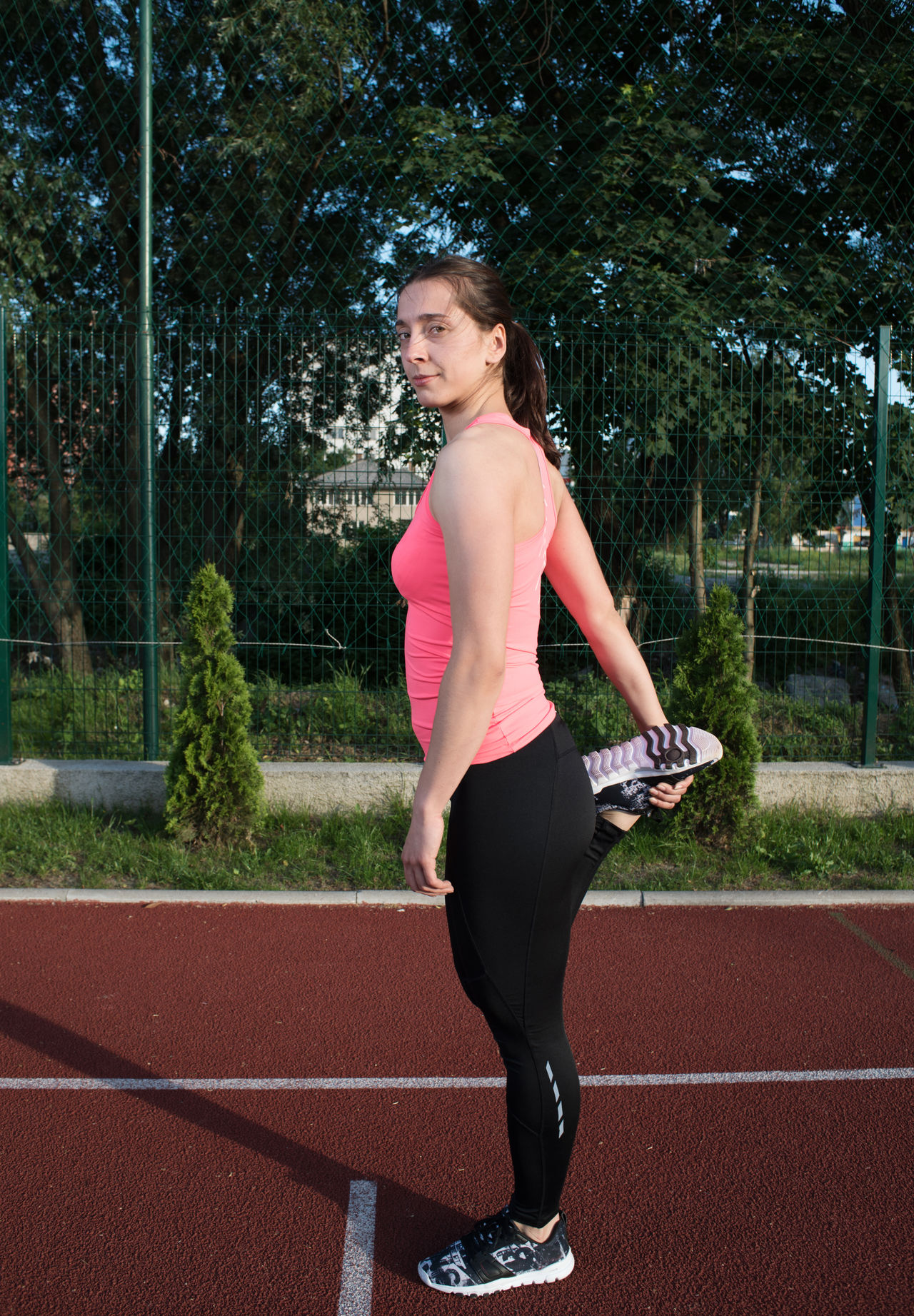 athlete stretching Adult Adults Only Athlete Challenge Day Exercising Full Length Human Body Part Lifestyles Looking Down One Person One Woman Only Only Women Outdoors People Pink Color Running Track Self Improvement Side View Sport Sports Clothing Sports Track Sports Training Standing Vitality