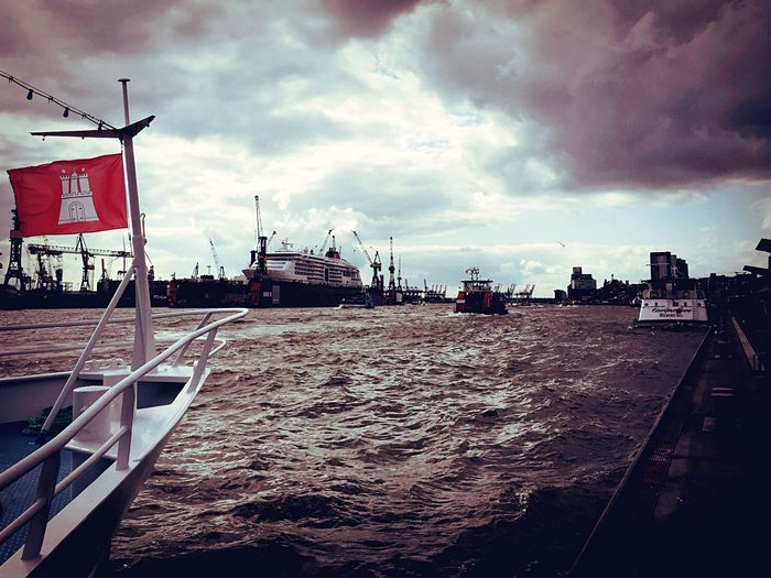 Sky Cloud - Sky Water Nautical Vessel Transportation Flag Mode Of Transport Harbor Sea Day Outdoors Architecture Built Structure Moored No People Mast Nature Building Exterior City Romantic Scenery Elbe River Port Of Hamburg  Landungsbrücken, Hamburg Heavy Clouds Harbour View The Week On EyeEm
