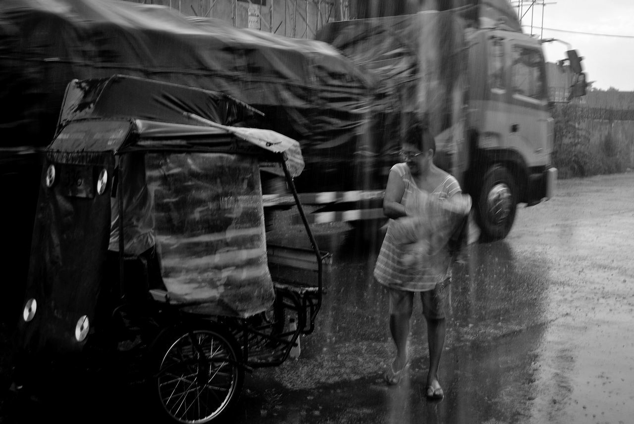 rain, real people, street, rainy season, wet, walking, motion, rear view, road, outdoors, full length, two people, shelter, day, under, transportation, lifestyles, men, below, building exterior, architecture, city, low section, people