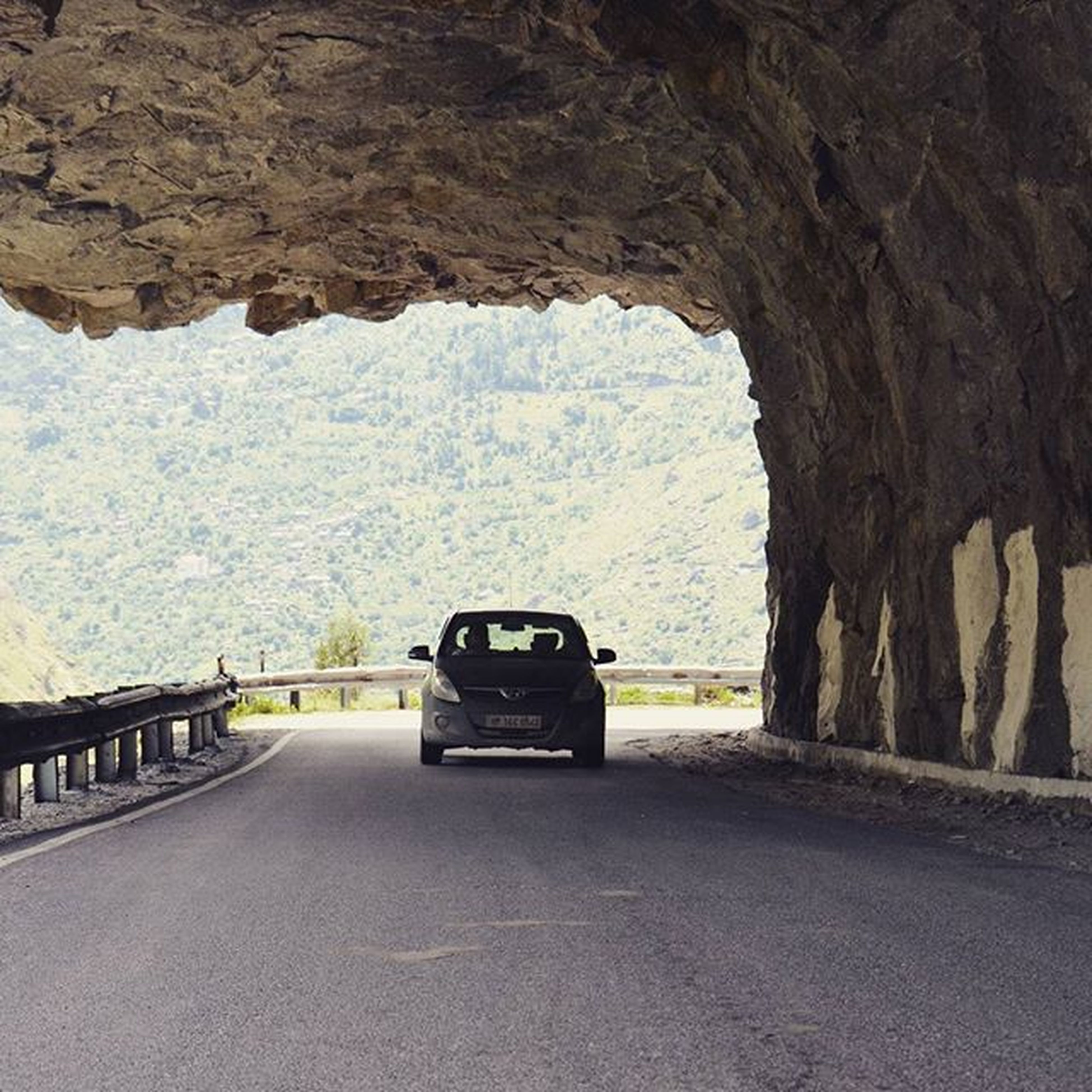 transportation, road, the way forward, car, mountain, tree, street, day, land vehicle, rock formation, empty, nature, diminishing perspective, arch, rock - object, tranquility, travel, no people, tranquil scene, indoors