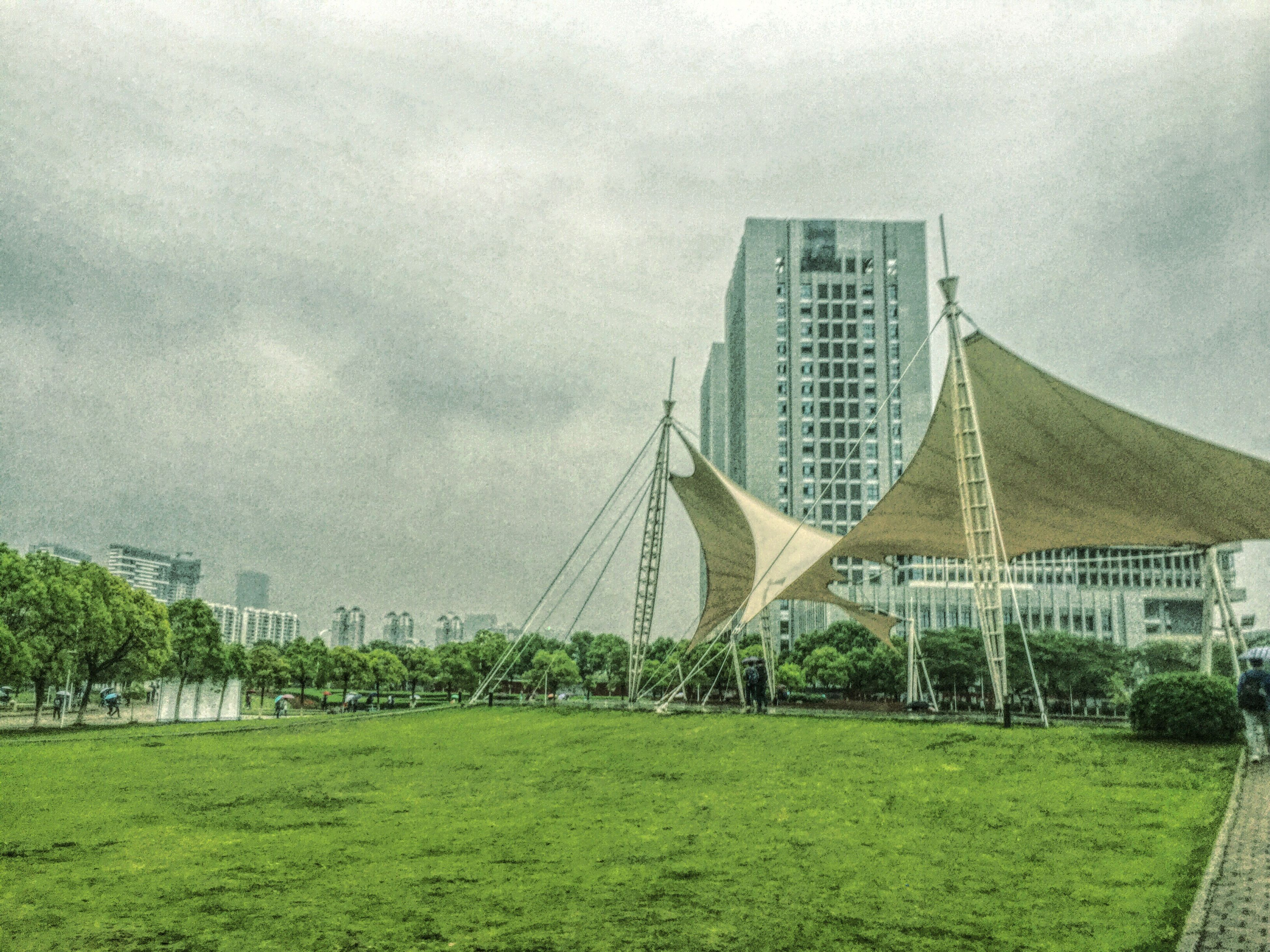 grass, sky, architecture, building exterior, built structure, cloud - sky, field, green color, cloudy, grassy, tree, day, outdoors, low angle view, cloud, no people, plant, nature, growth, modern