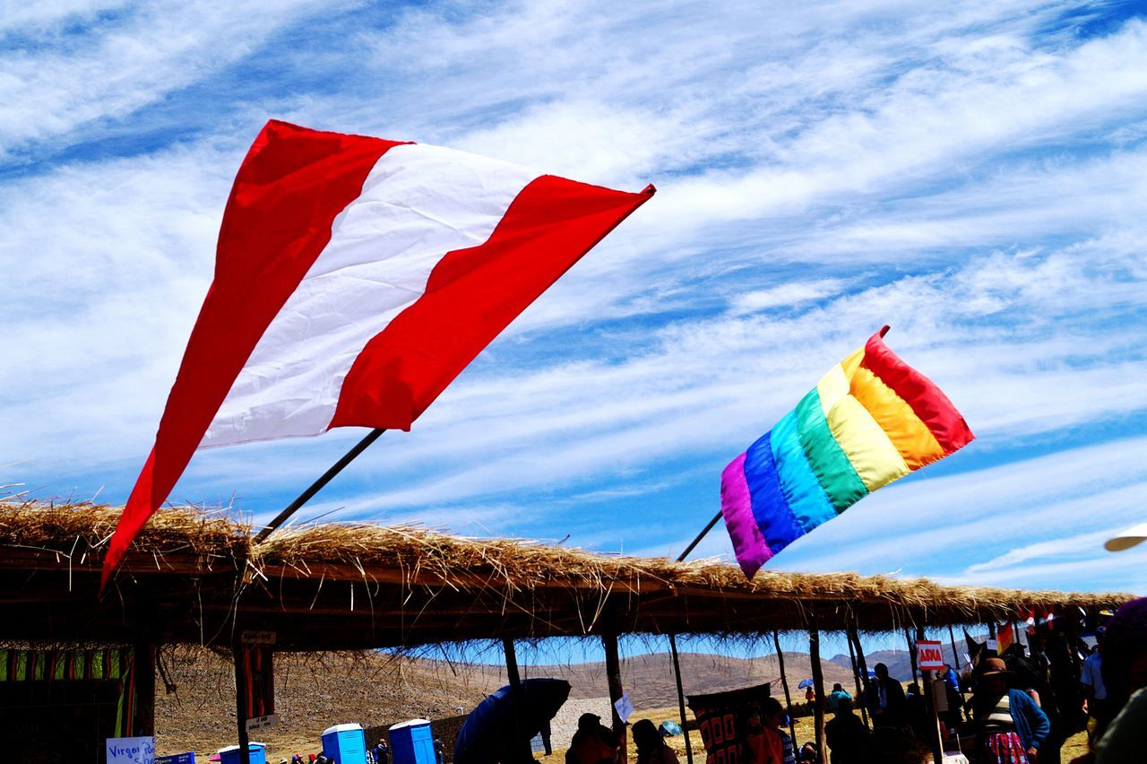flag, patriotism, sky, national flag, identity, multi colored, cloud - sky, umbrella, american flag, beach umbrella, wind, striped, parasol, cloud, red, hanging, variation, celebration, colorful, low angle view
