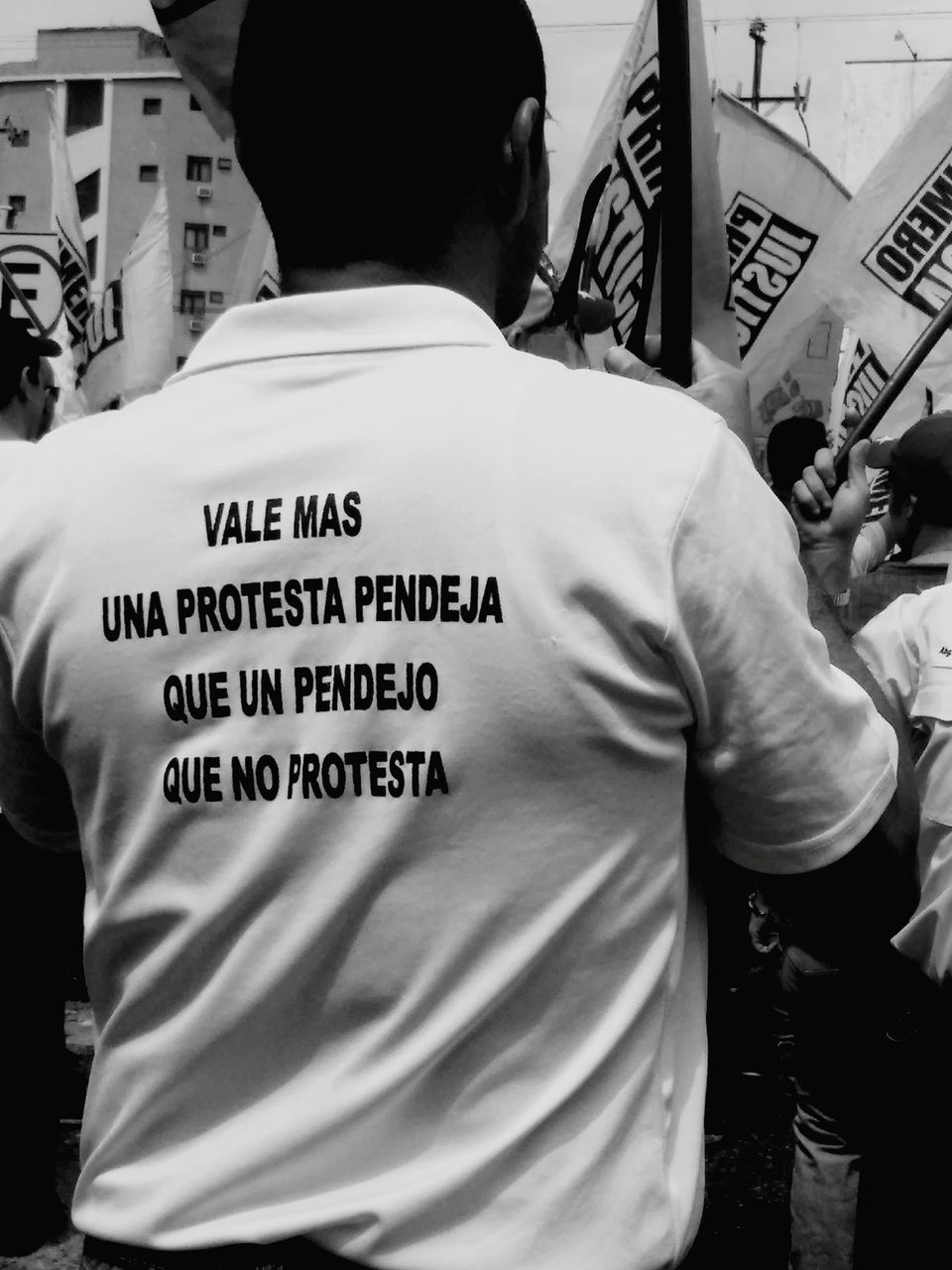 text, western script, communication, protest, rear view, real people, placard, men, street, protestor, day, outdoors, city, one person, riot, adult, people