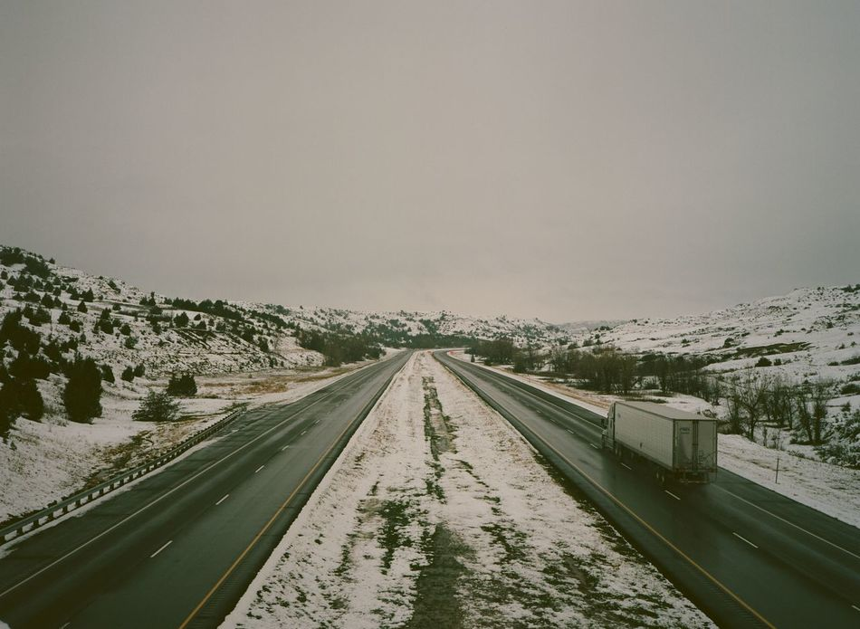 Looking down on an empty, snowy highway with one truck. Beauty In Nature Country Road Countryside Day Diminishing Perspective Empty Growth Landscape Long Nature No People Outdoors Road Road Marking Road Trip Scenics Sky Snow Snowy The Way Forward Tranquil Scene Tranquility Tree Vanishing Point Weather