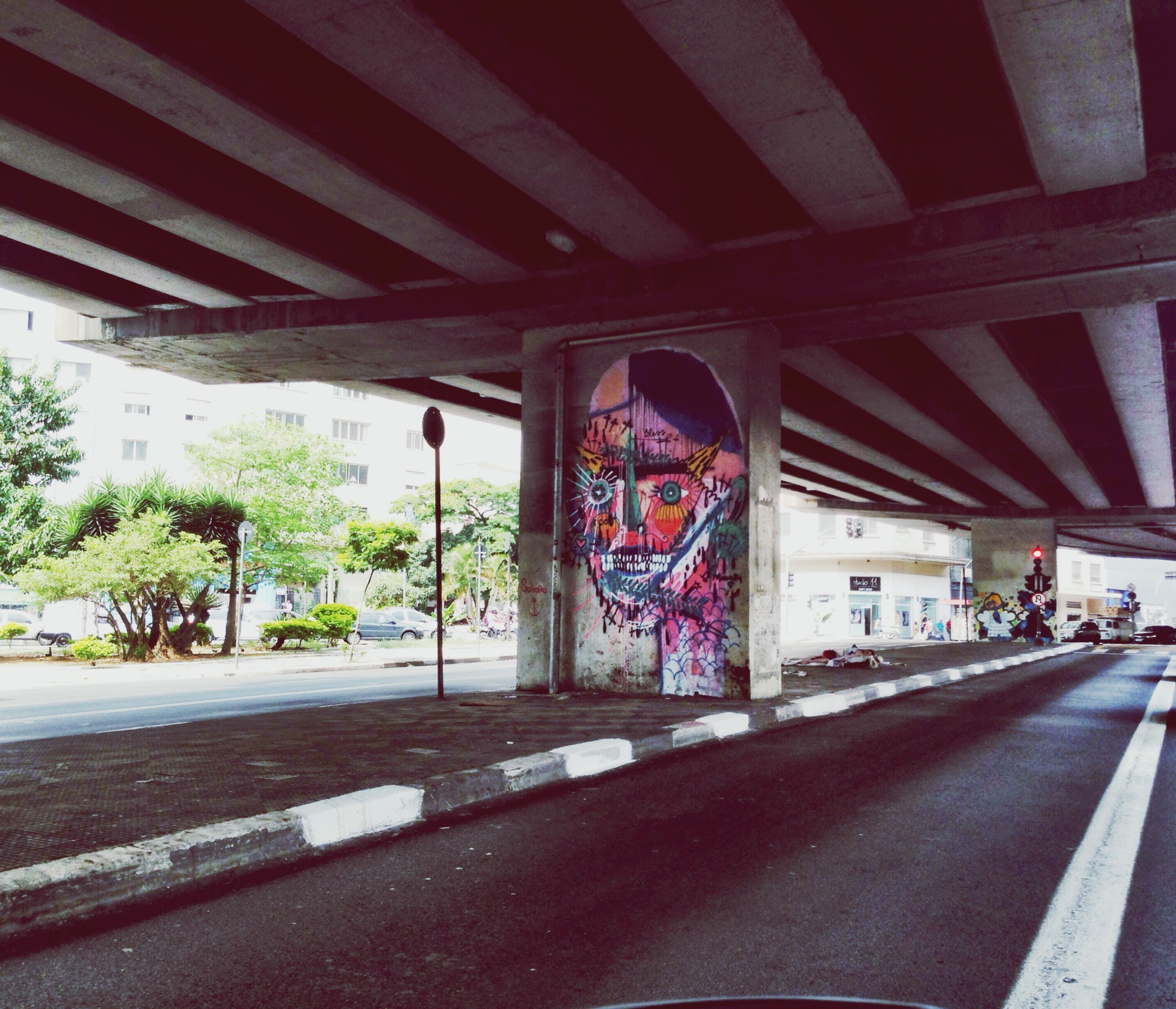 architecture, built structure, road, street, building exterior, graffiti, transportation, road marking, art, text, city, art and craft, creativity, car, incidental people, day, the way forward, wall - building feature, outdoors, sidewalk