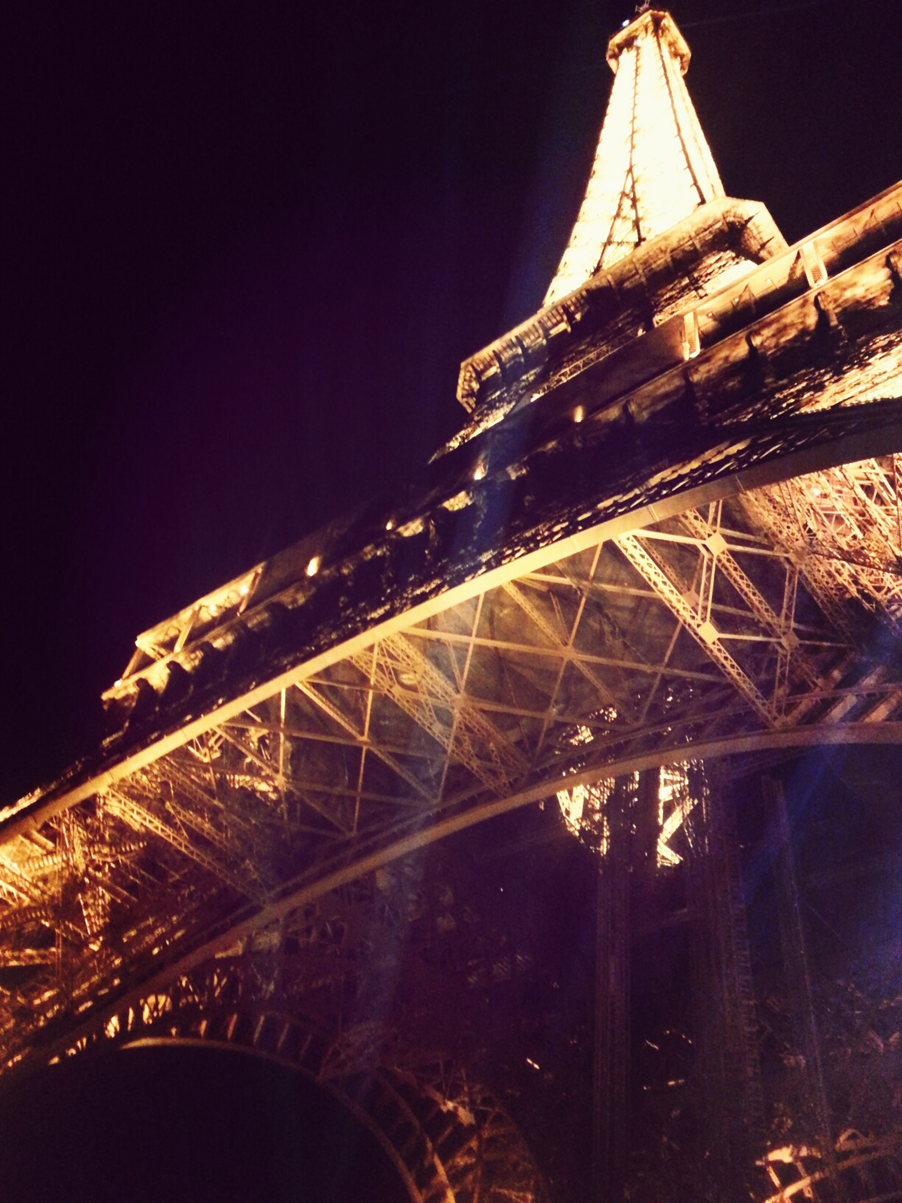 architecture, built structure, famous place, international landmark, travel destinations, night, tourism, capital cities, eiffel tower, travel, low angle view, tower, clear sky, illuminated, building exterior, tall - high, culture, history, city, engineering