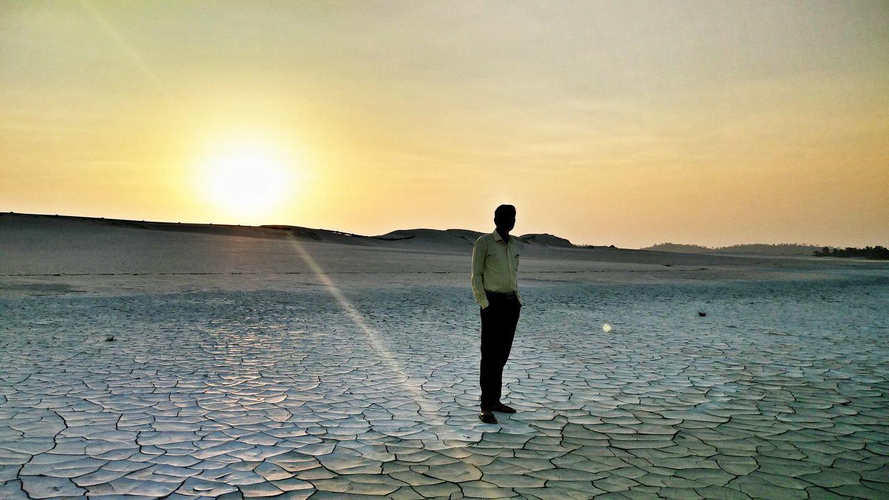sunset, real people, scenics, nature, one person, beauty in nature, standing, sun, outdoors, tranquil scene, water, sky, leisure activity, full length, lifestyles, landscape, tranquility, sea, vacations, mountain, day, people