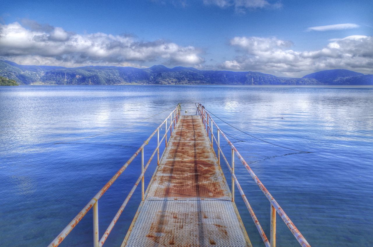 Pier Over River In Front Of Mountains Against Blue Sky