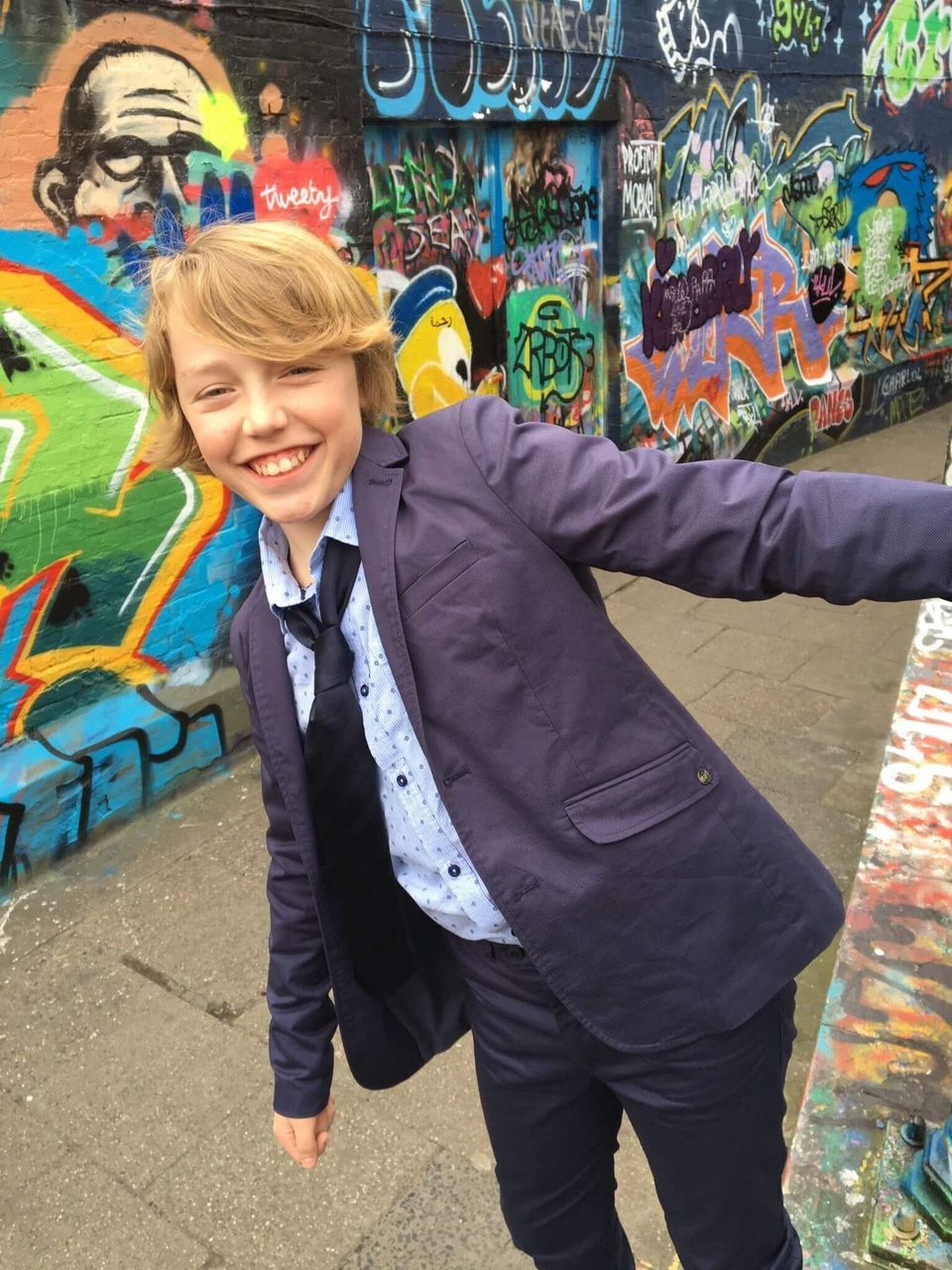 smiling, graffiti, happiness, real people, fun, looking at camera, portrait, multi colored, full length, leisure activity, childhood, day, one person, outdoors, cheerful, boys, lifestyles, standing, young adult, people