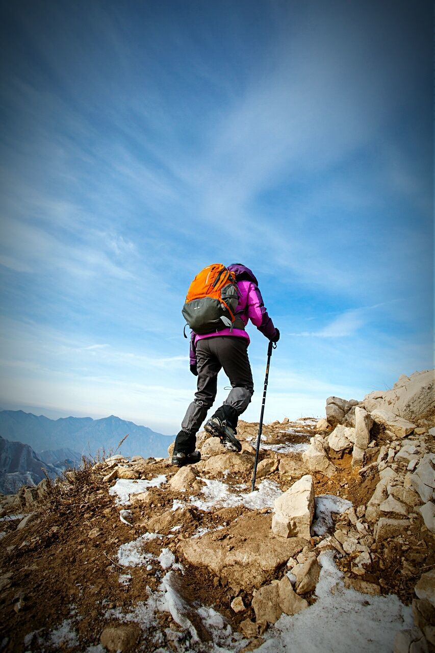 Rear View Of Hiker Climbing Mountain Against Sky