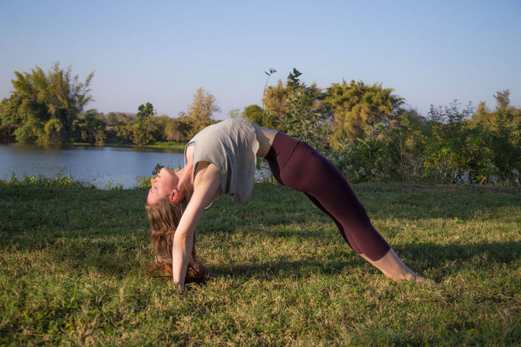 Adult Adults Only Day Flexibility Full Length Grass Green Lifestyles Mature Adult Nature One Person One Woman Only Only Women Outdoor Photography Outdoors Outside People River Riverside Tree Women Yoga Yoga Pose Yoga ॐ Yogagirl