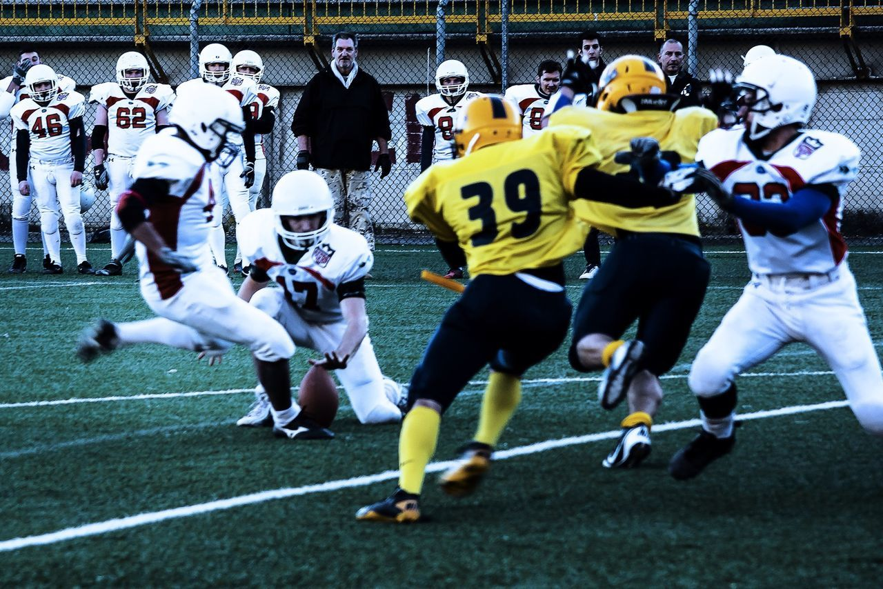real people, defending, competition, competitive sport, protection, large group of people, men, sport, headwear, sports helmet, lifestyles, sports clothing, teamwork, sports uniform, day, sports team, outdoors, american football player