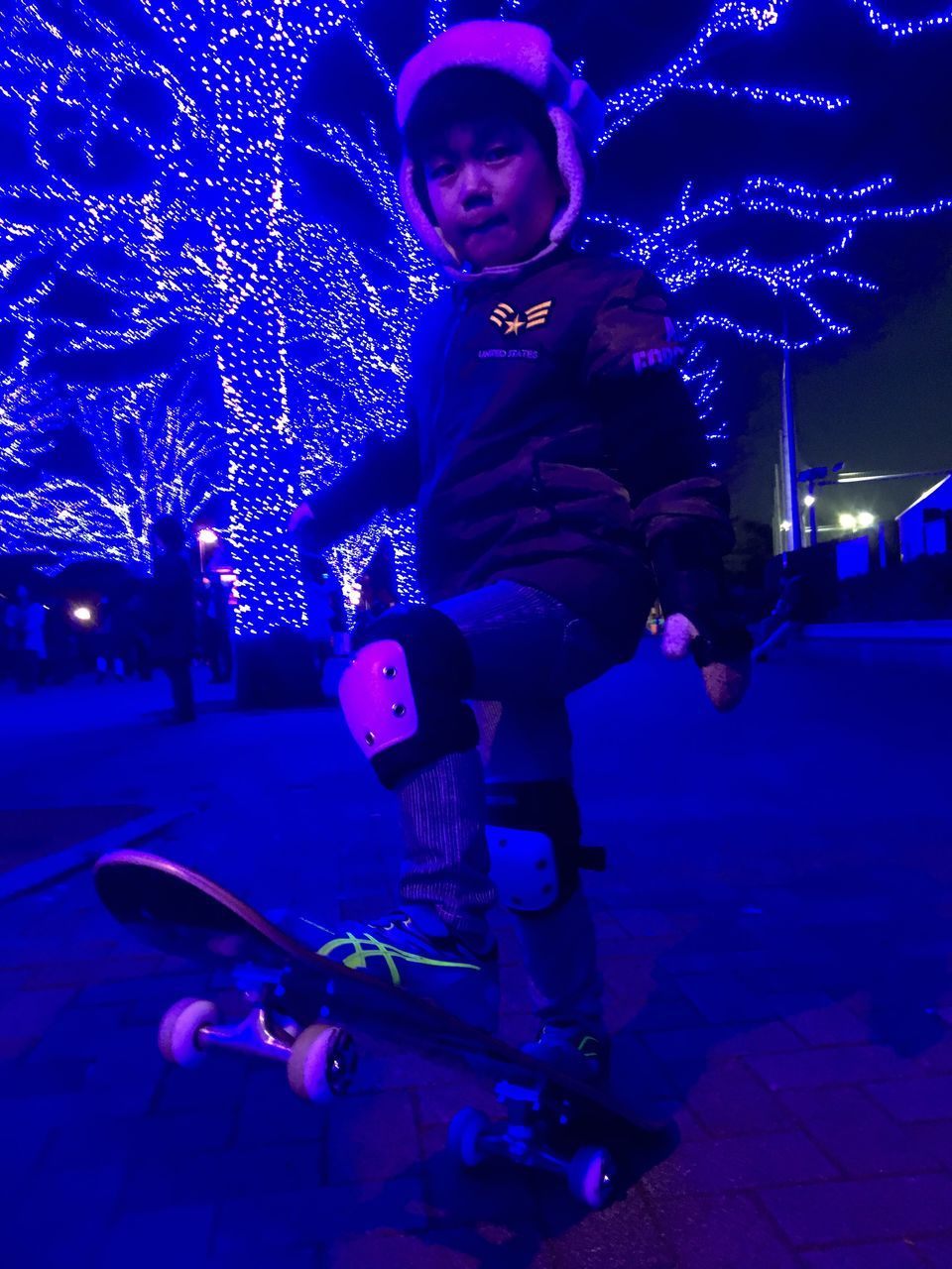 night, full length, illuminated, real people, one person, young adult, lifestyles, front view, leisure activity, street, young women, outdoors, city life, warm clothing, city, christmas lights, looking at camera, portrait, building exterior, ice skate, blue, architecture, sky, people