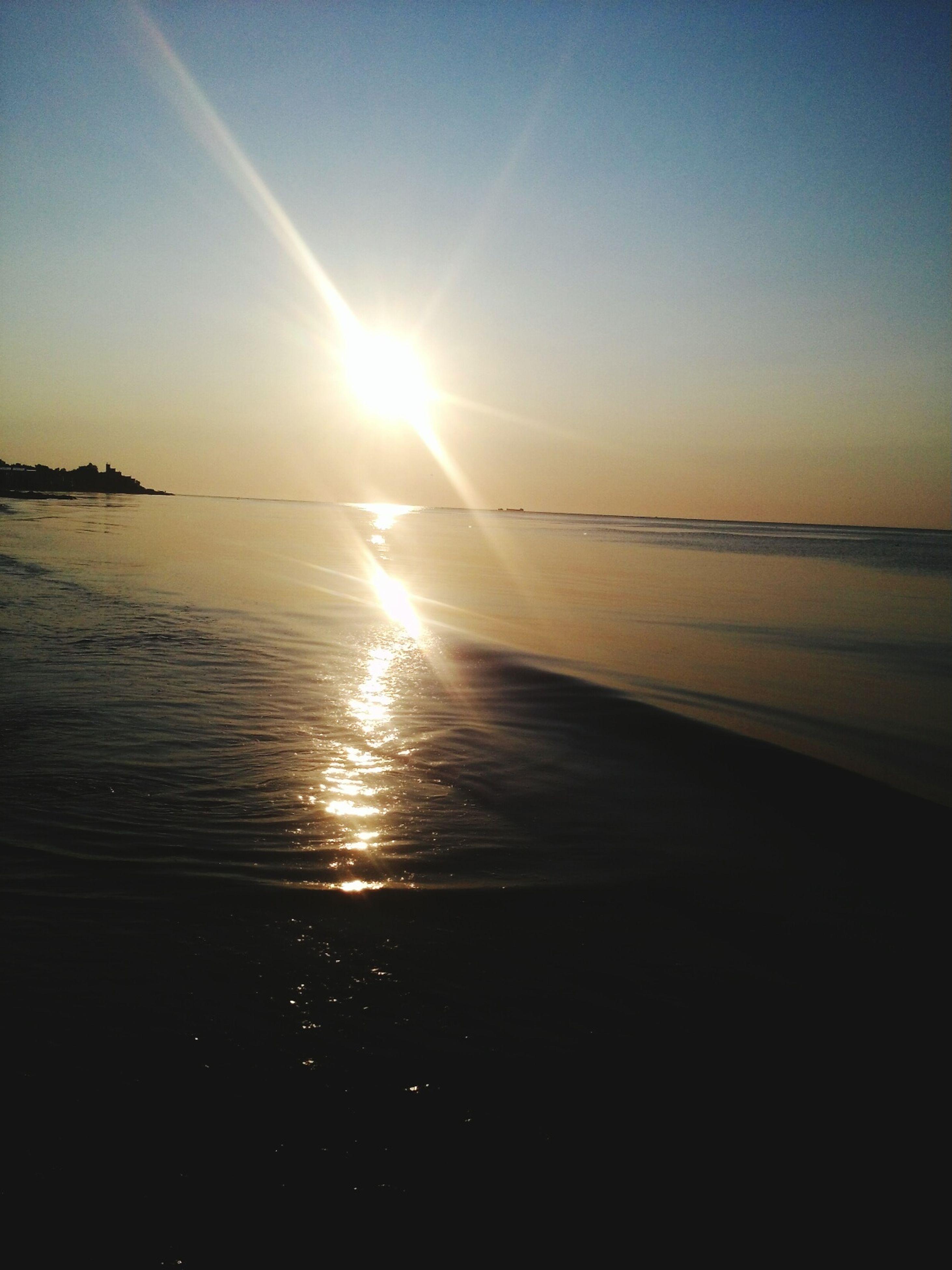 sea, water, horizon over water, sun, beach, tranquil scene, scenics, sunset, tranquility, beauty in nature, shore, reflection, sunlight, sky, nature, idyllic, sunbeam, sand, clear sky, outdoors
