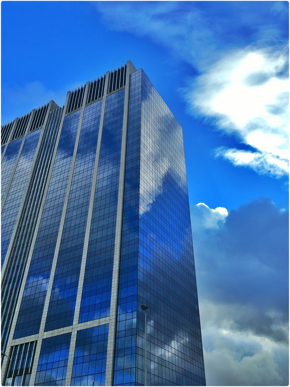 Low Angle View Of Modern Glass Office Skyscraper Against Sky