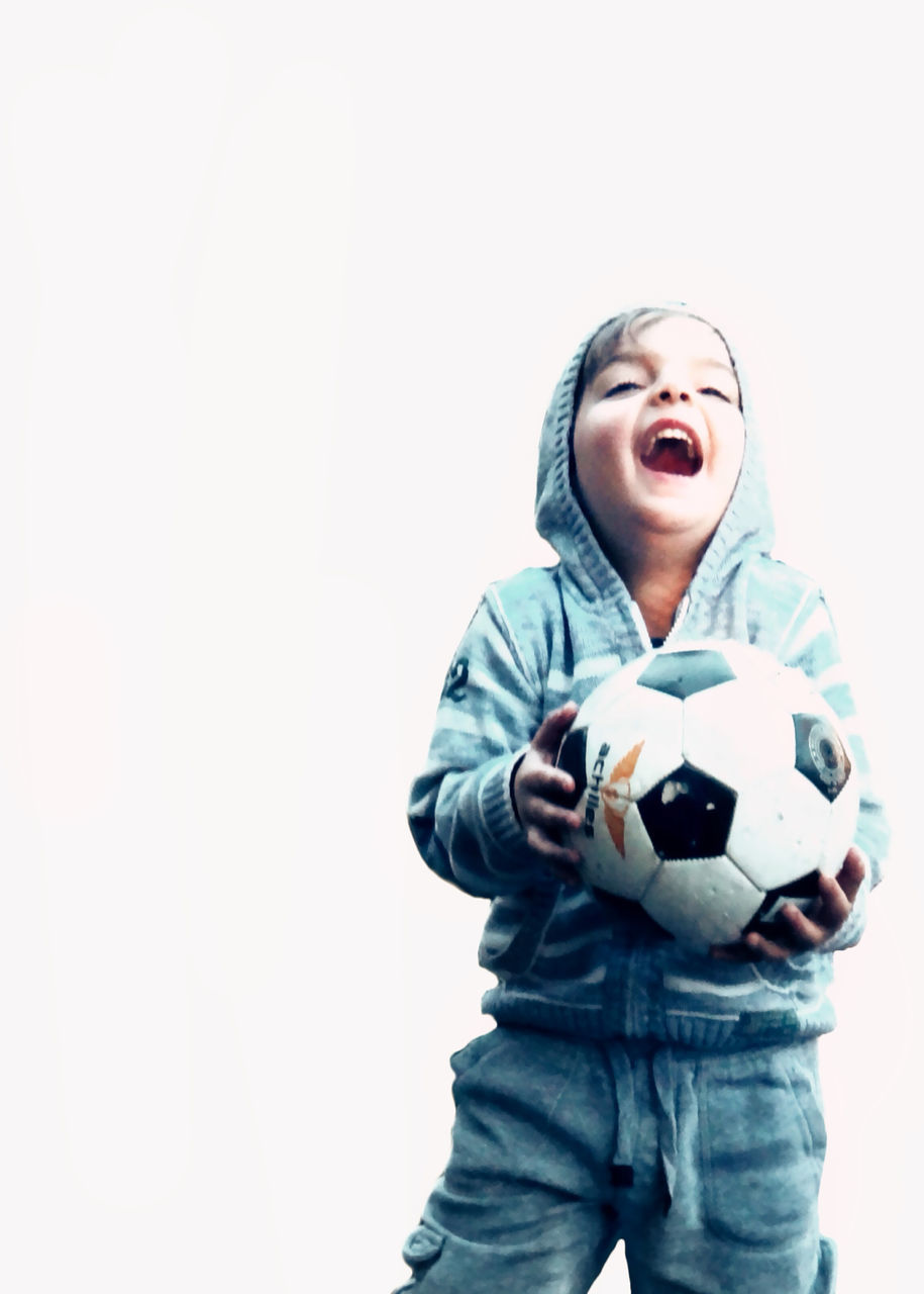 mouth open, white background, leisure activity, real people, front view, boys, studio shot, one person, elementary age, three quarter length, screaming, soccer, lifestyles, shouting, casual clothing, soccer ball, childhood, fun, happiness, clear sky, sport, portrait, outdoors, fan - enthusiast, young adult, day, people