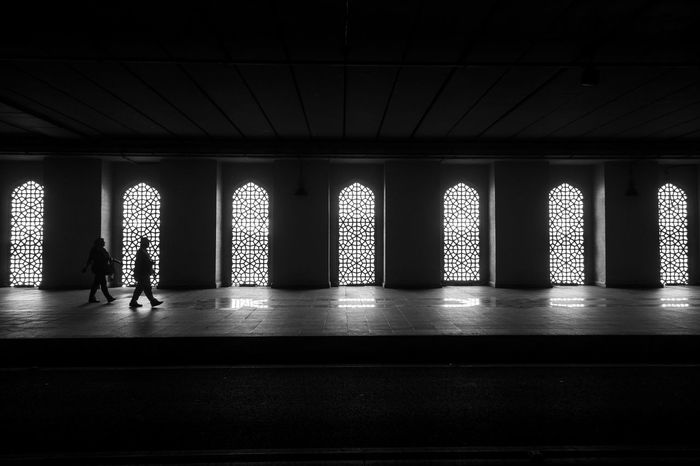 Two people walking past a row of arches Arches Architecture Black & White Blackandwhite Bnw Dark Darkness And Light Indoors  Silhouettes The Street Photographer - 2017 EyeEm Awards Two People Walking Windows Streetphotography Islamic Architecture Islamic Design