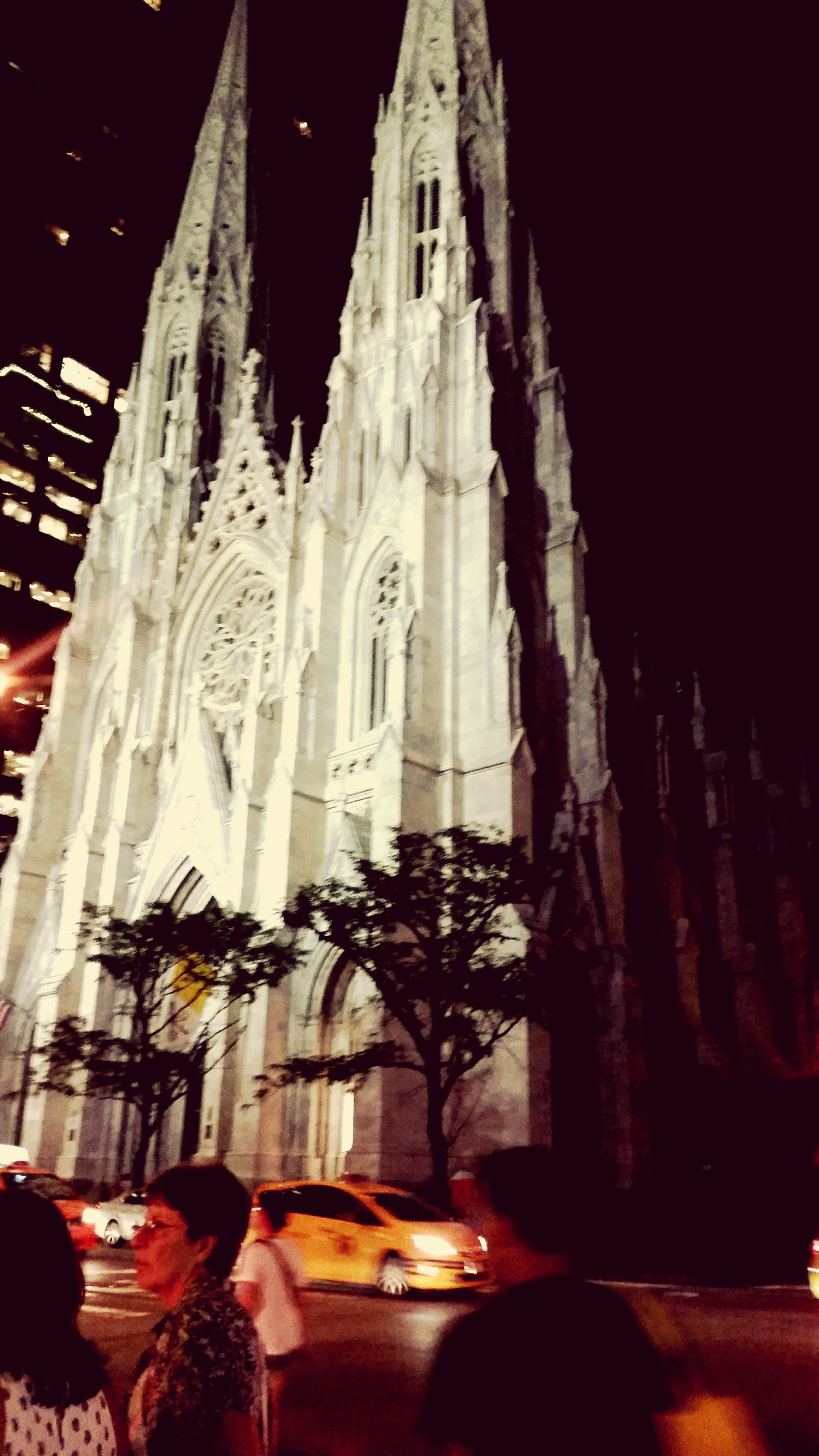 architecture, building exterior, built structure, night, religion, place of worship, illuminated, spirituality, church, city, travel destinations, low angle view, cathedral, street, famous place, incidental people, facade, history