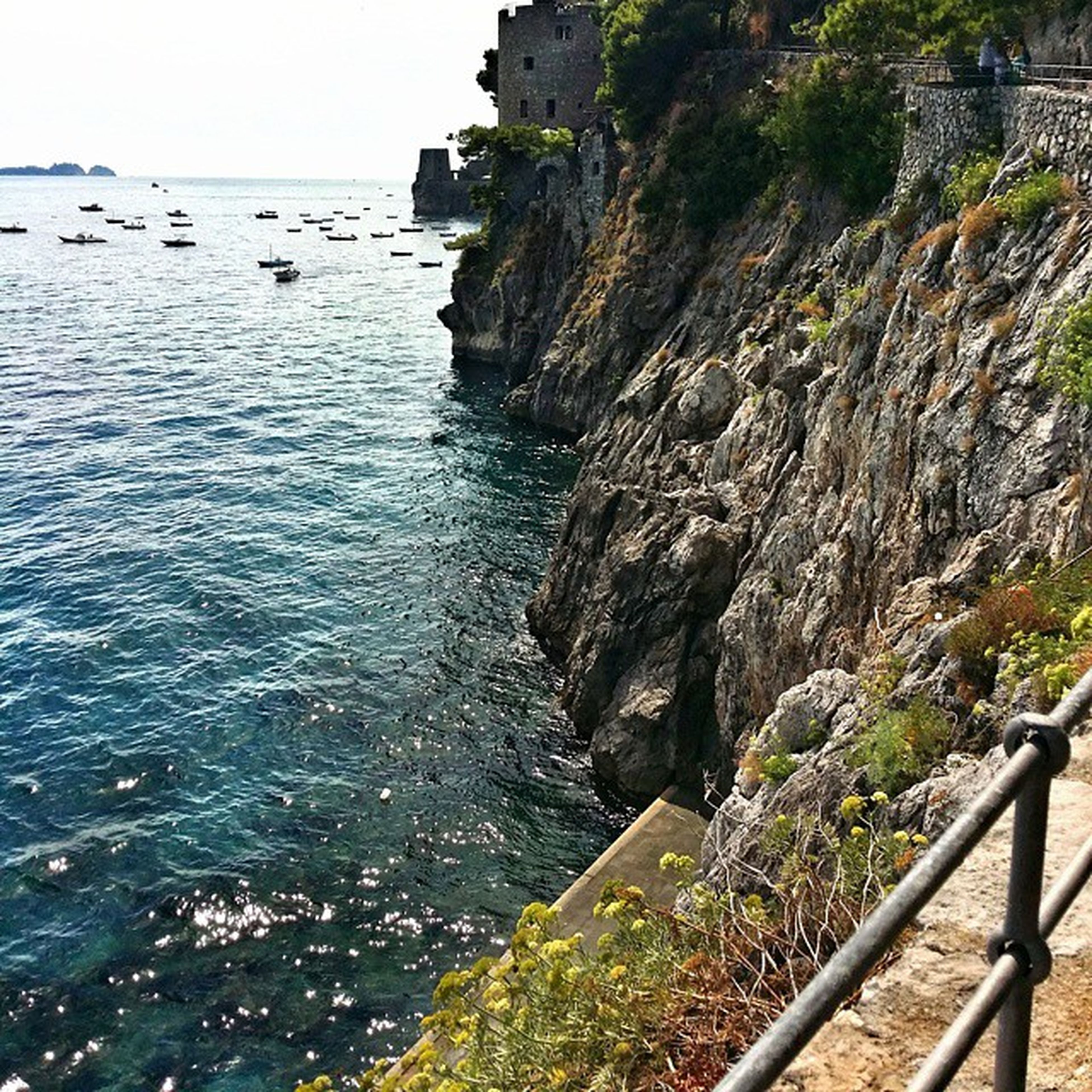 water, sea, tranquil scene, scenics, tranquility, horizon over water, high angle view, beauty in nature, nature, mountain, coastline, railing, rock - object, cliff, rock formation, shore, idyllic, day, beach, built structure