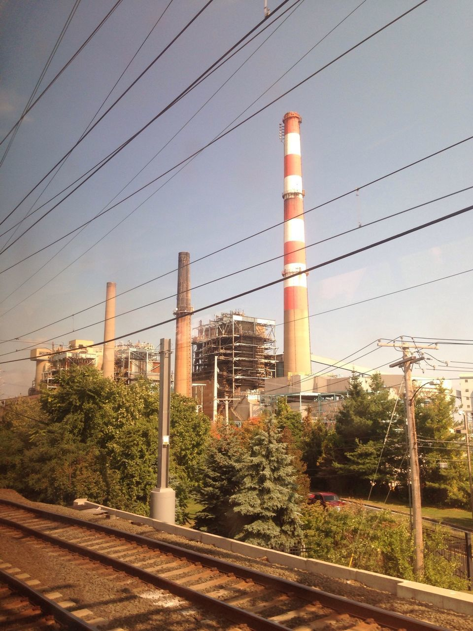 cable, connection, tree, power line, no people, electricity pylon, electricity, fuel and power generation, architecture, industry, railroad track, built structure, factory, smoke stack, sky, outdoors, clear sky, day