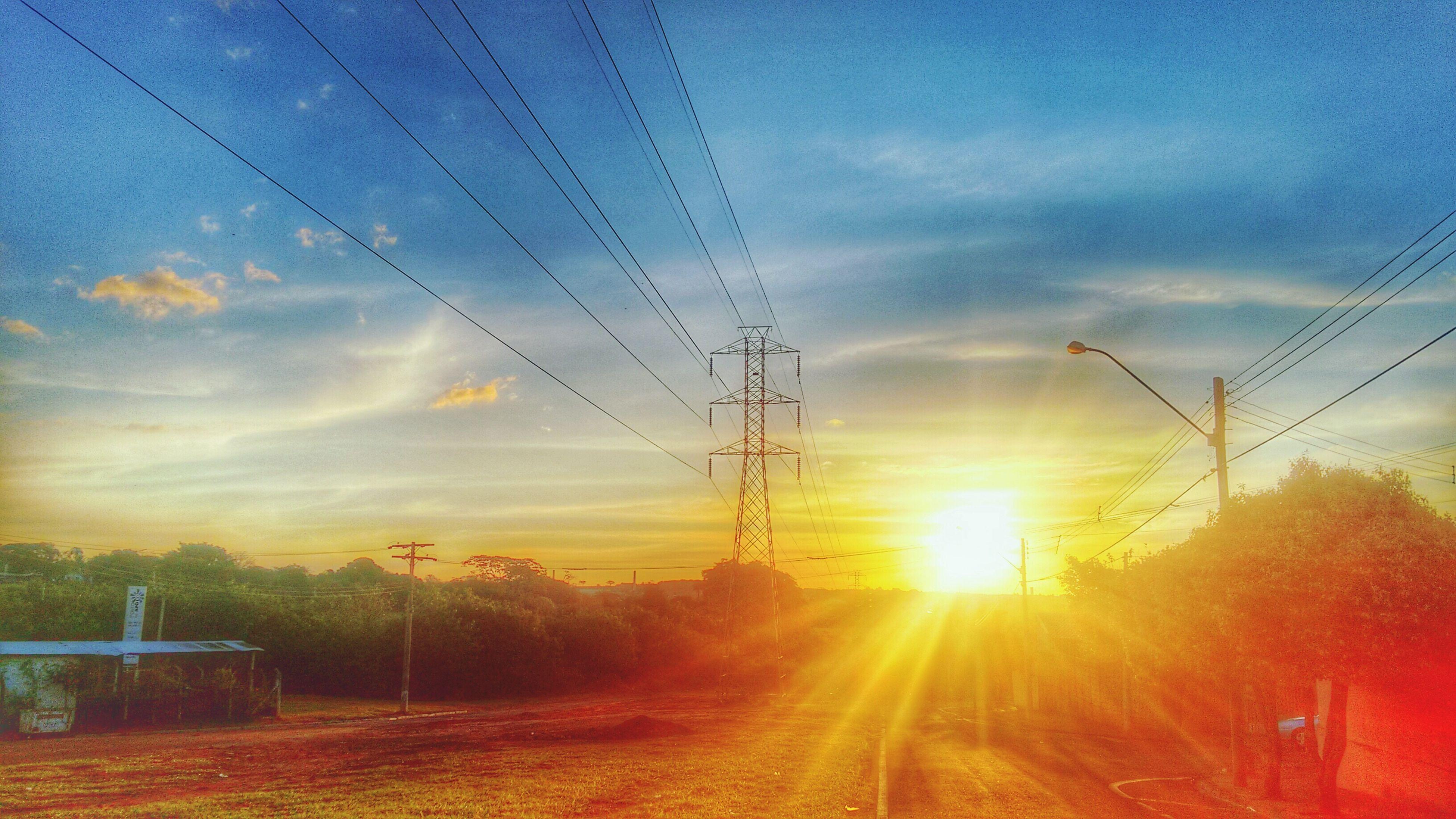 power line, electricity pylon, sky, sunset, electricity, power supply, cloud - sky, sun, cable, landscape, cloud, connection, fuel and power generation, nature, orange color, field, transportation, tranquility, power cable, sunlight