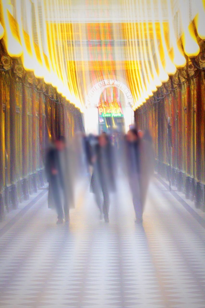 blurred motion, walking, men, indoors, real people, architecture, large group of people, women, built structure, illuminated, motion, full length, the way forward, day, people