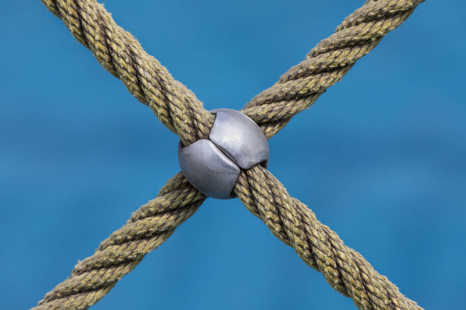 Close-up of crossed rope against blue background on a playground Blue Blue Background Close-up Crisscross Cross Shape Day Durability Focus On Foreground Jungle Gym Letter X Metal Metallic No People Outdoors Part Of Pattern Playground Rope Selective Focus Simplicity Sphere Strength Textured  Triangle Shape