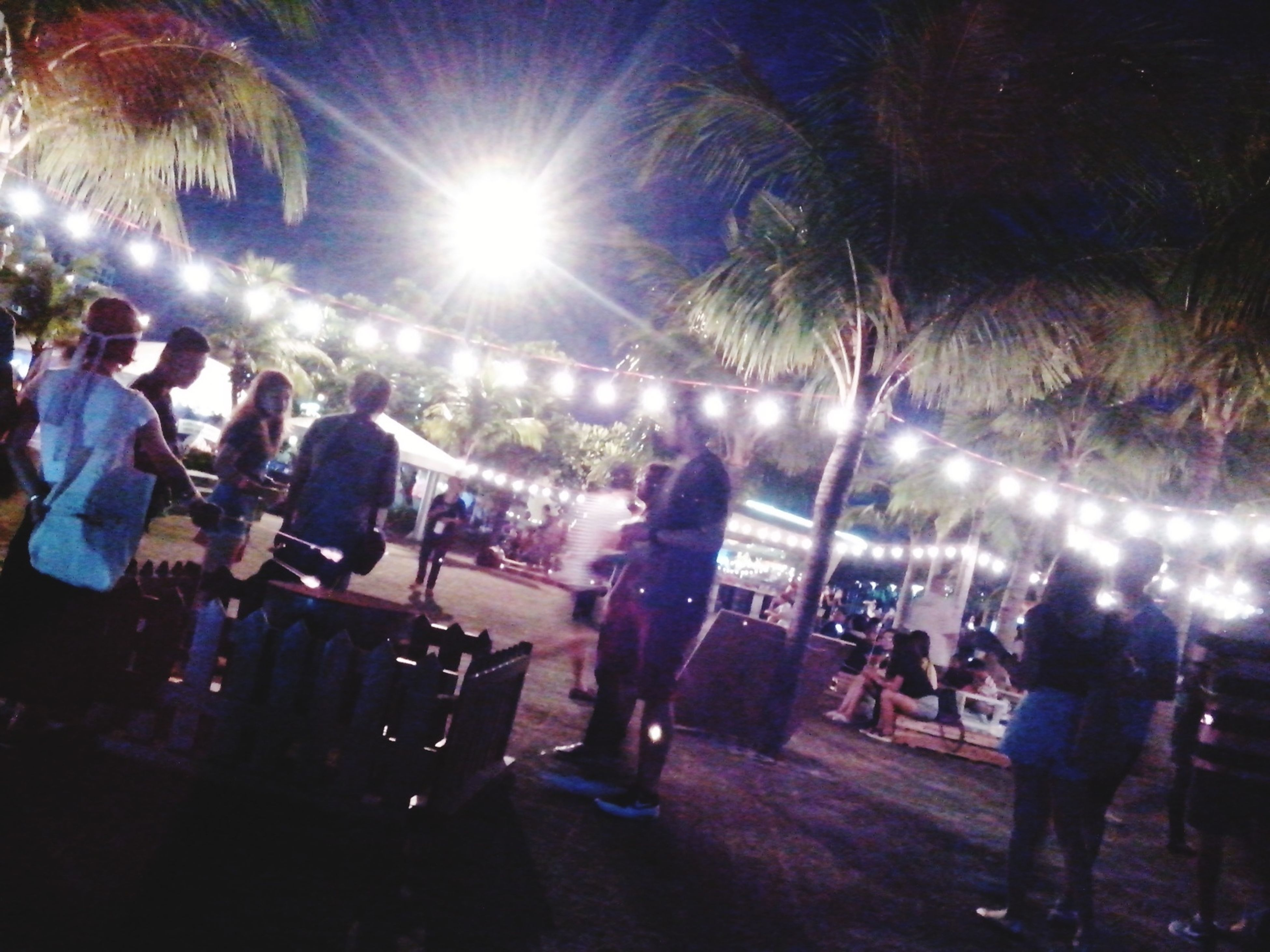 large group of people, lifestyles, leisure activity, crowd, person, men, illuminated, enjoyment, arts culture and entertainment, night, mixed age range, tree, celebration, event, city life, fun, street, togetherness, lighting equipment