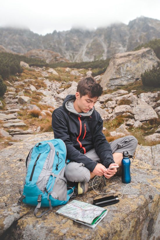 Boy resting on a rock and charging a mobile phone during a trip in mountains Activity Backpack Battery Bottle Boy Charge Charger Device Hike Hiker Map Mobile Mountains Nature Outdoors Phone Resting Rock Smart Summer Technology Tourism Travel Trip Vacations